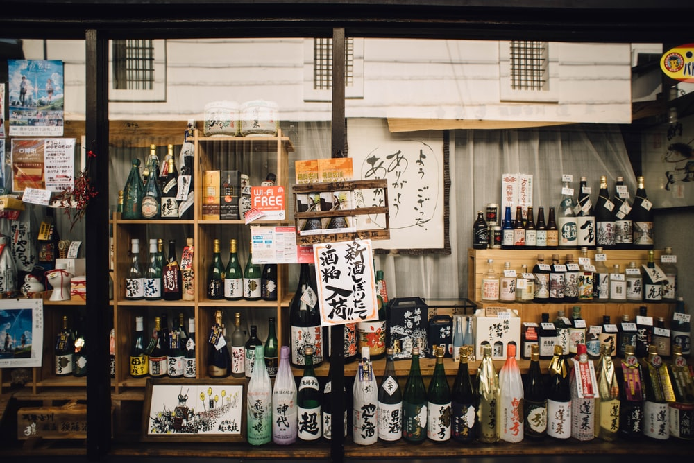 assorted glass bottles on wooden shelf