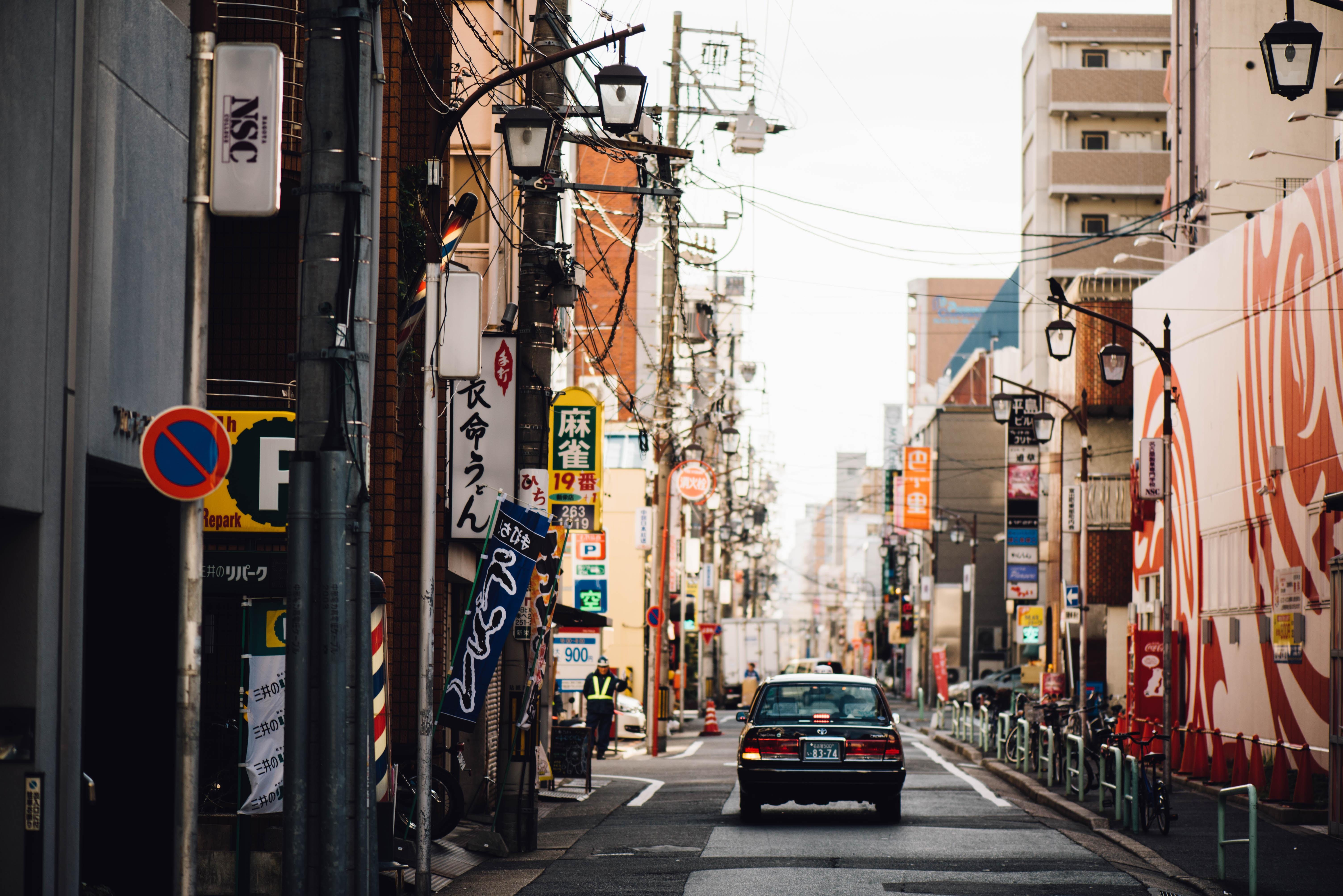 A car in a narrow street in an Asian city