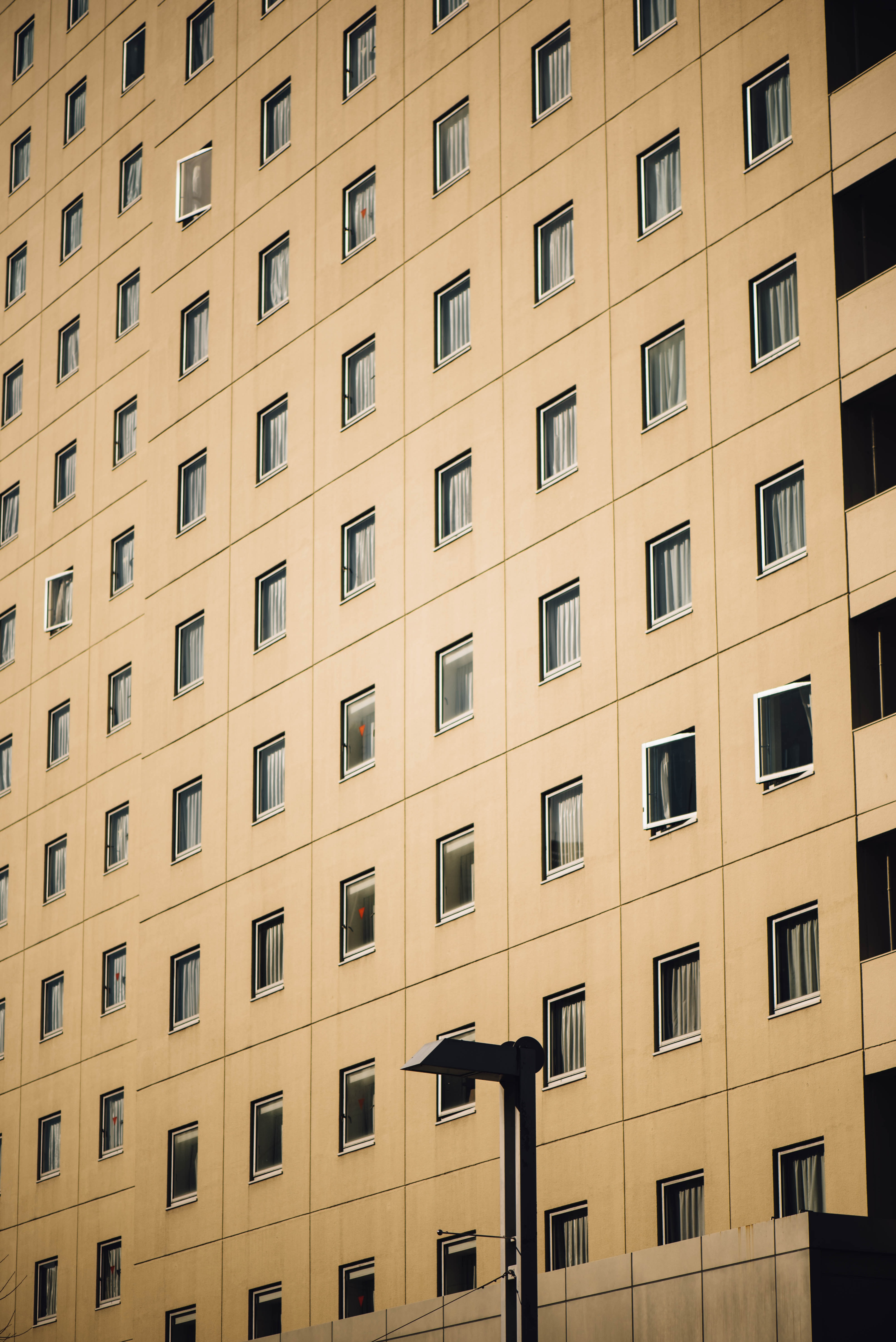 Rows of square windows on beige apartment building exterior