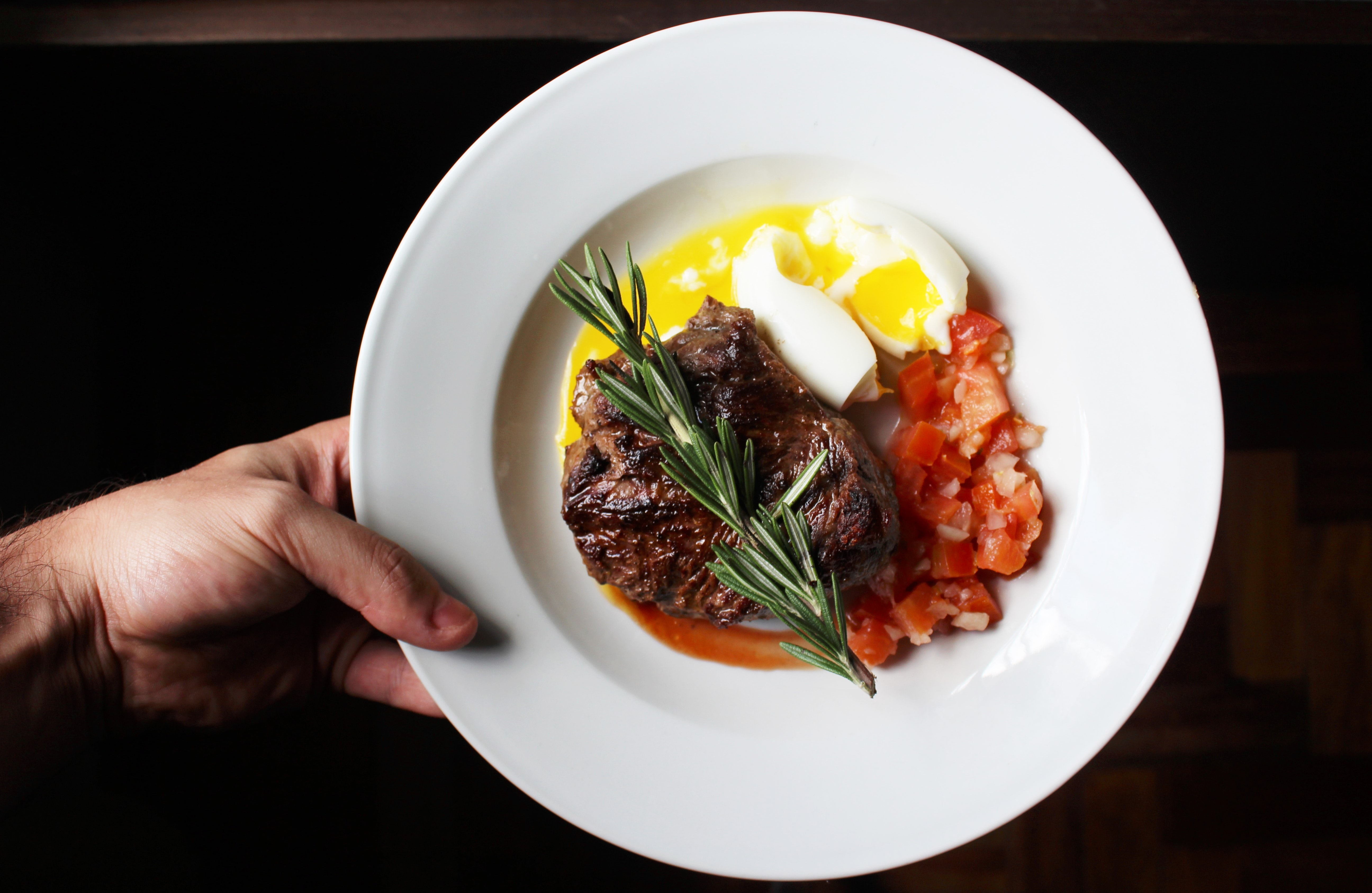 Hand holds a plate of steak, soft boiled egg, and tomatoes