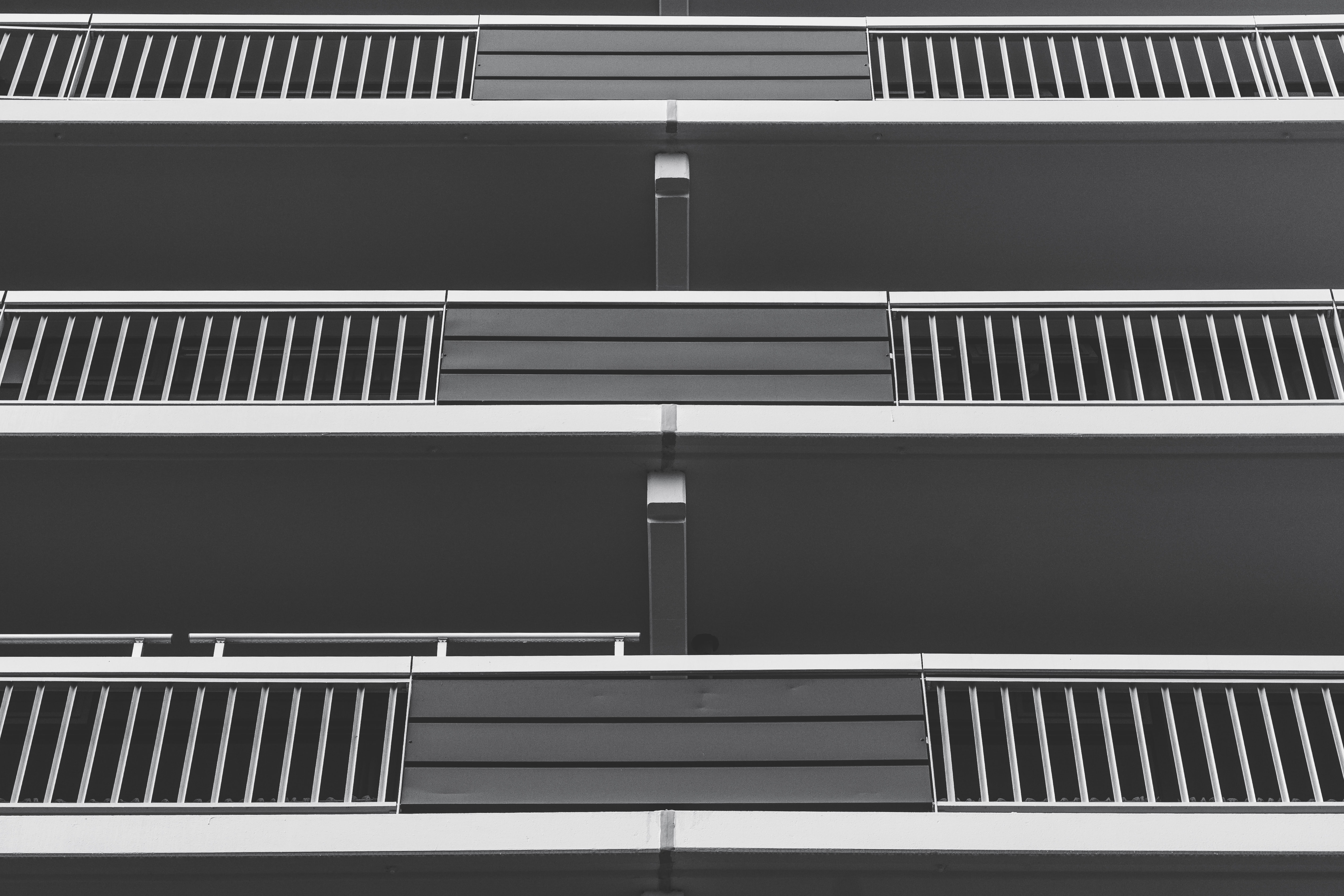 Black and white shot of apartment building balconies from below