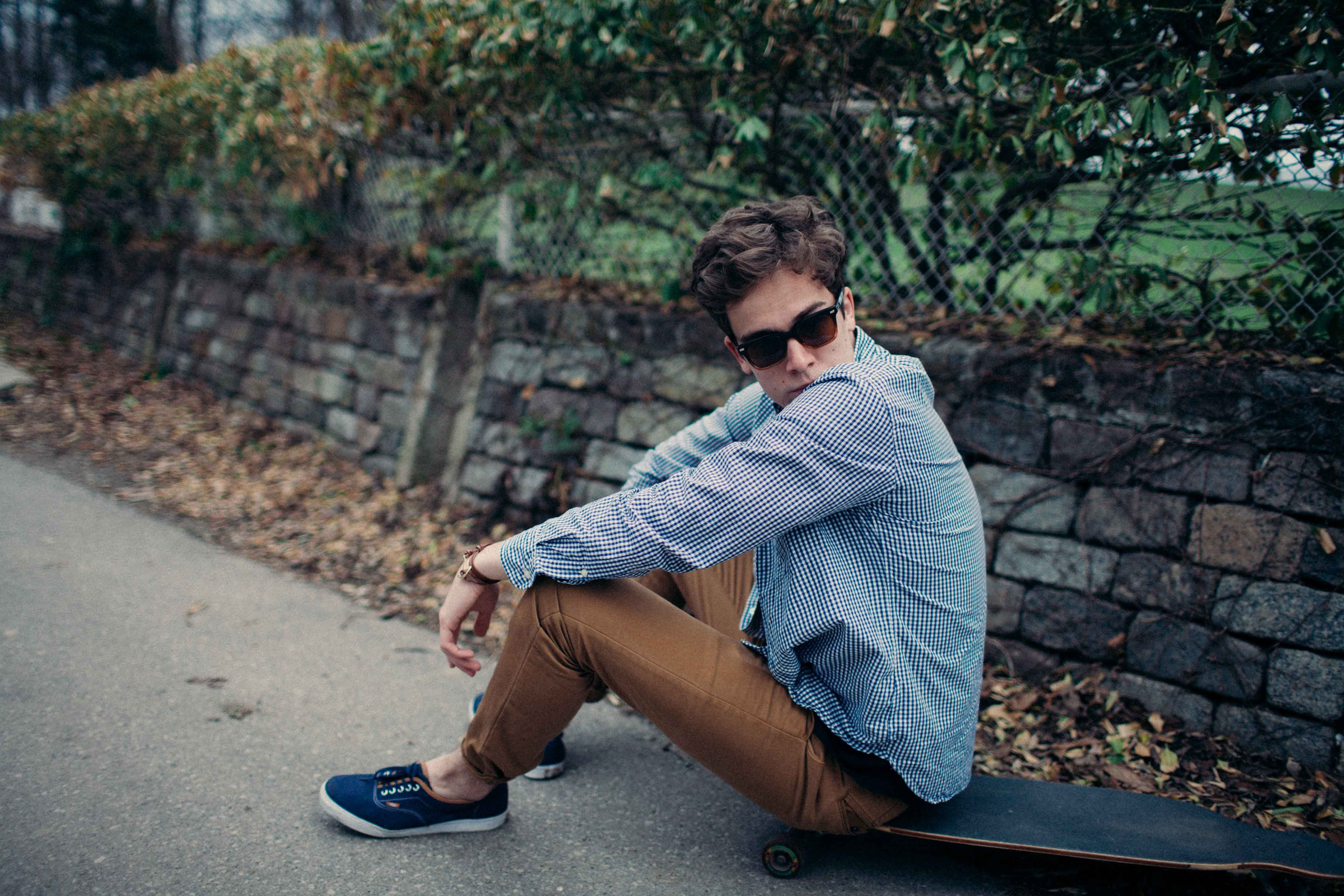 man sitting on skateboard during daytime