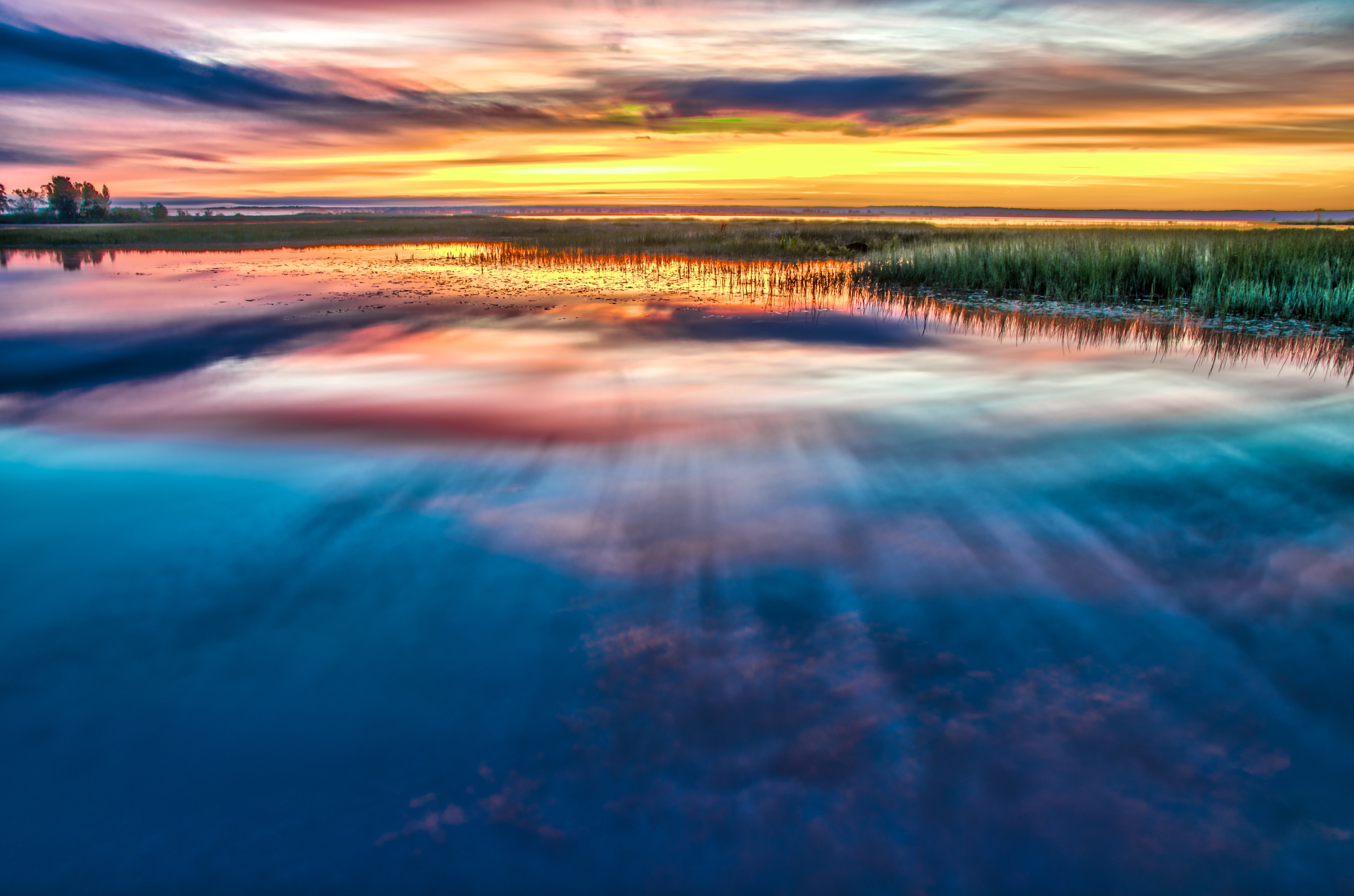 A reflection of the colorful sunset in the lake surrounded by grass