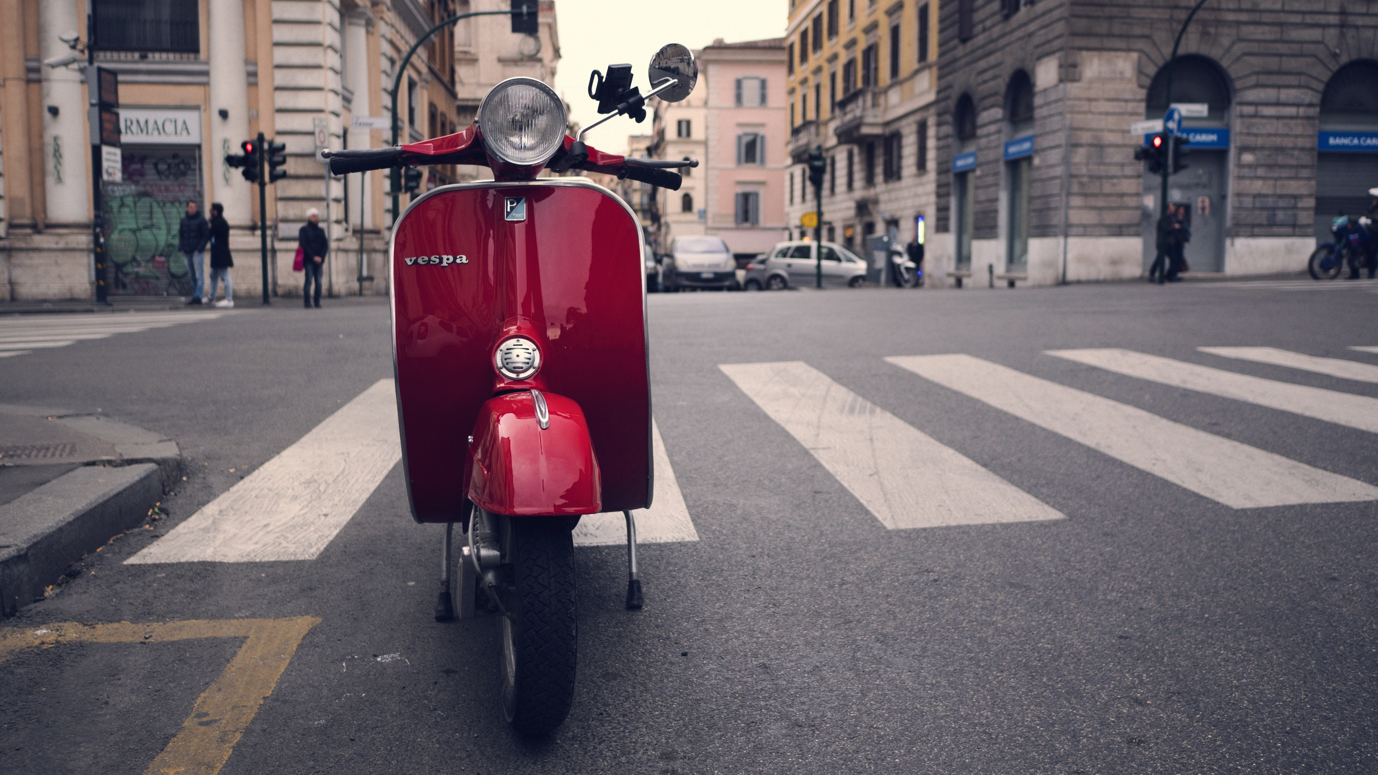 Red vespa scooter parked on a city street in Rome