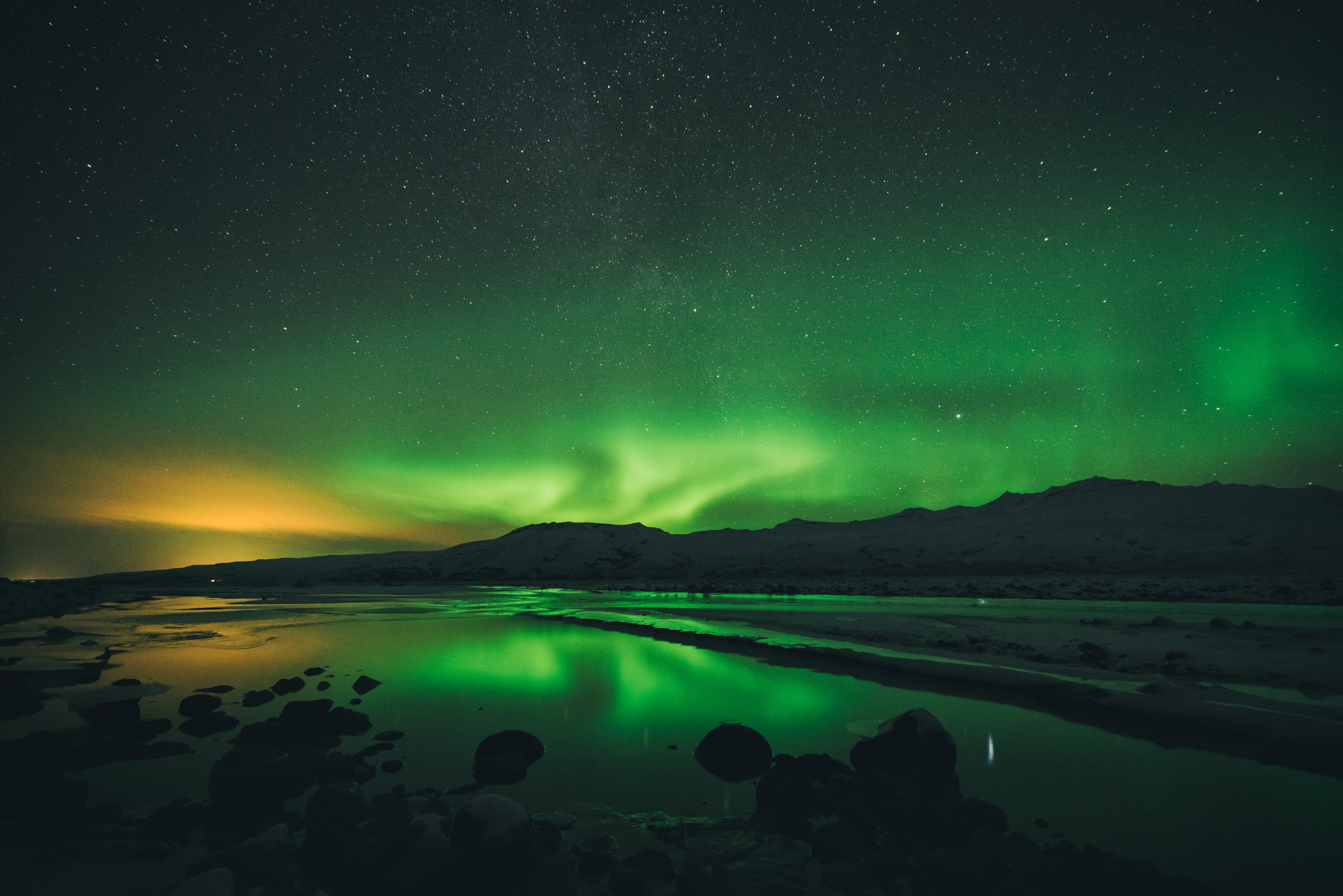 Colorful orange and green Northern Lights being reflected on the water surface in Thórsmörk.