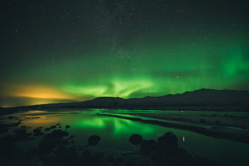 calm of water near mountain under aurora borealis at night time
