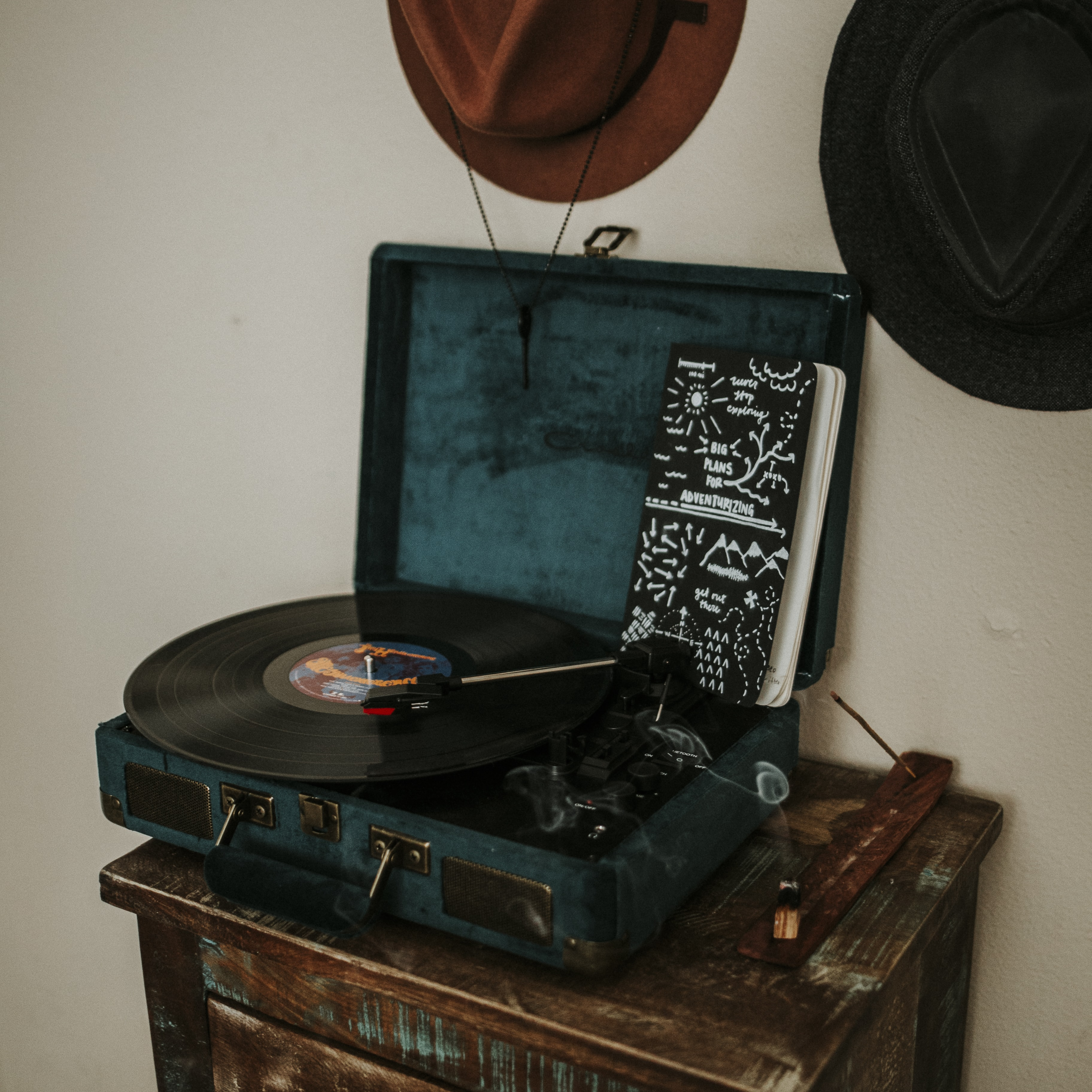 Turntable in blue velvet case with record on a table near hats on the wall