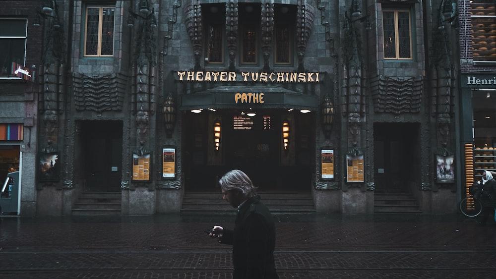 man standing near Theater Tuschinski building