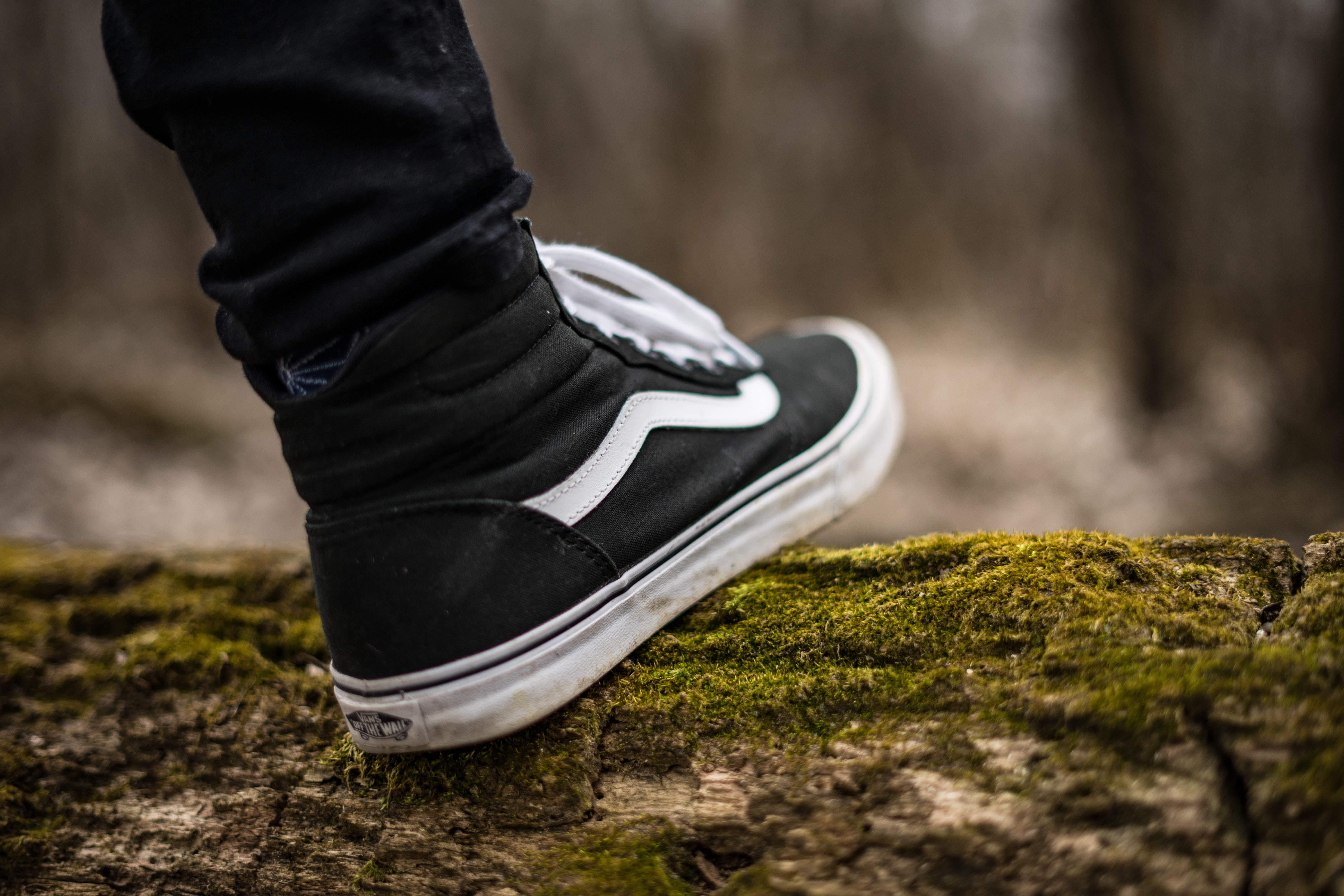 person wearing black and white Vans Sk8-Hi