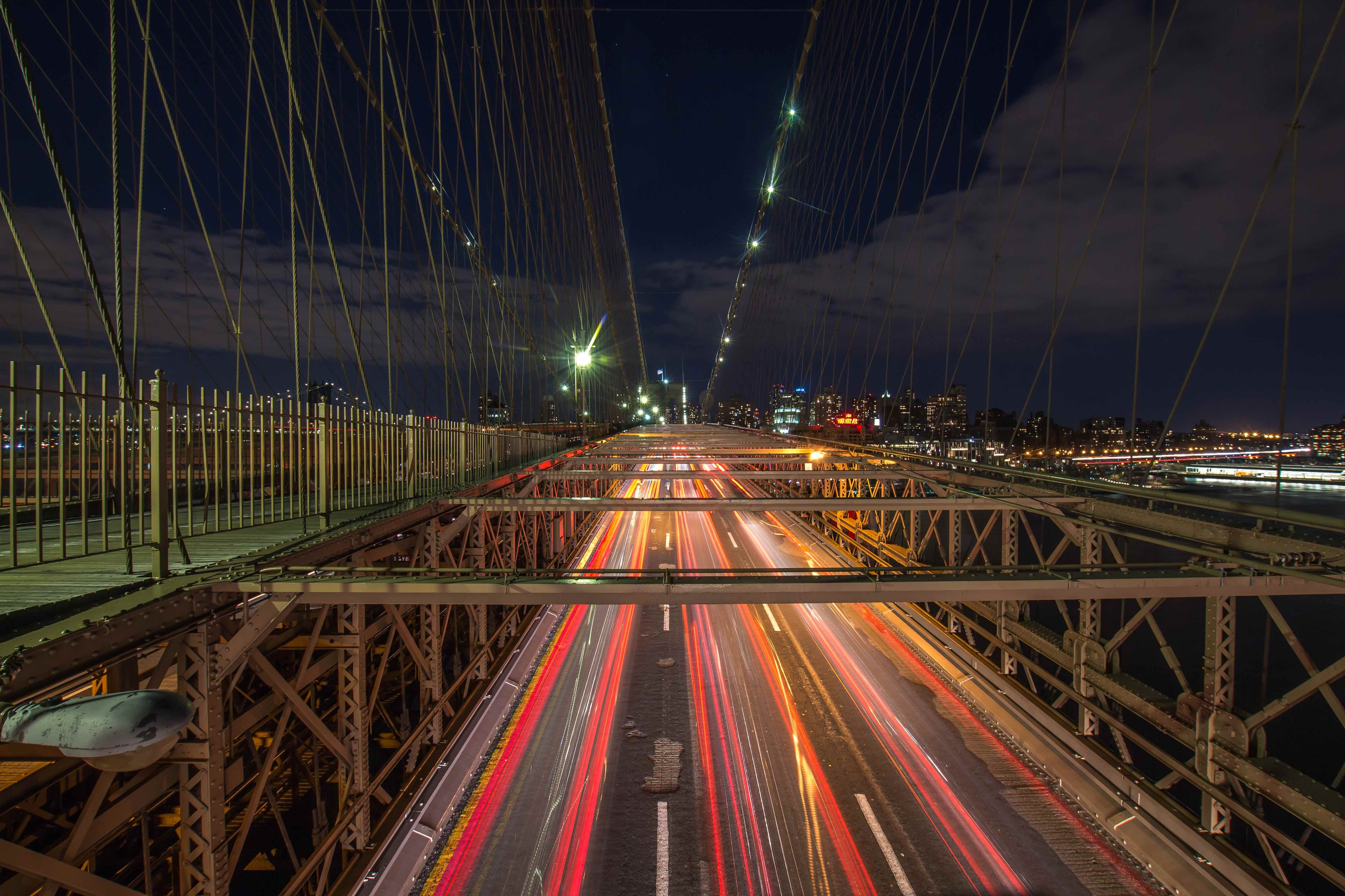 A night-time shot of the Brooklyn Bridge with eccentric traffic light trails
