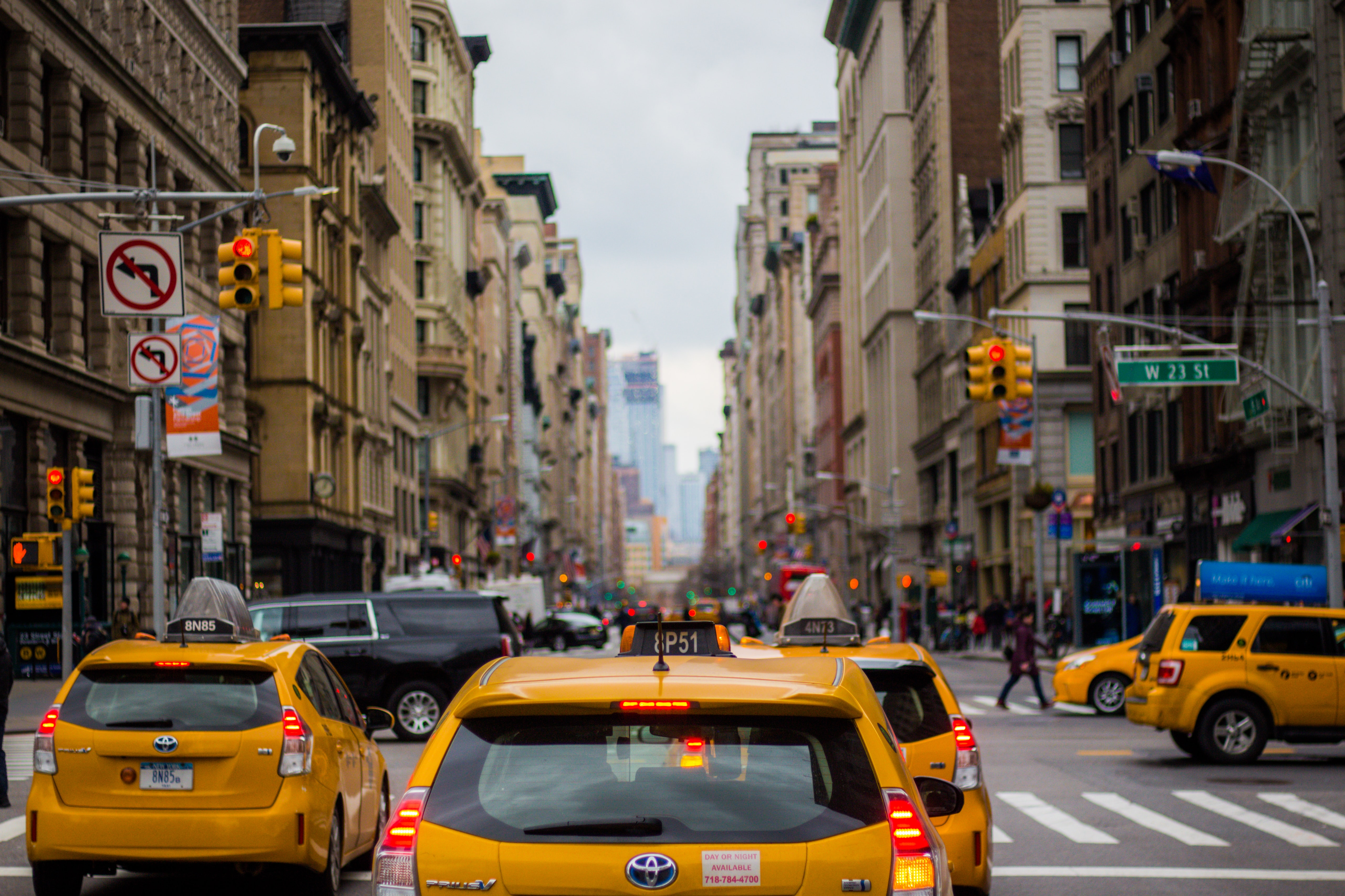 Taxi cabs stop at a red light at a busy intersection in downtown Manhattan