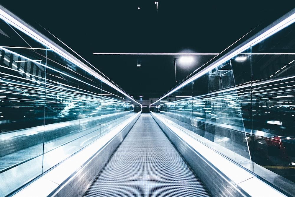 gray conveyor between glass frames at nighttime