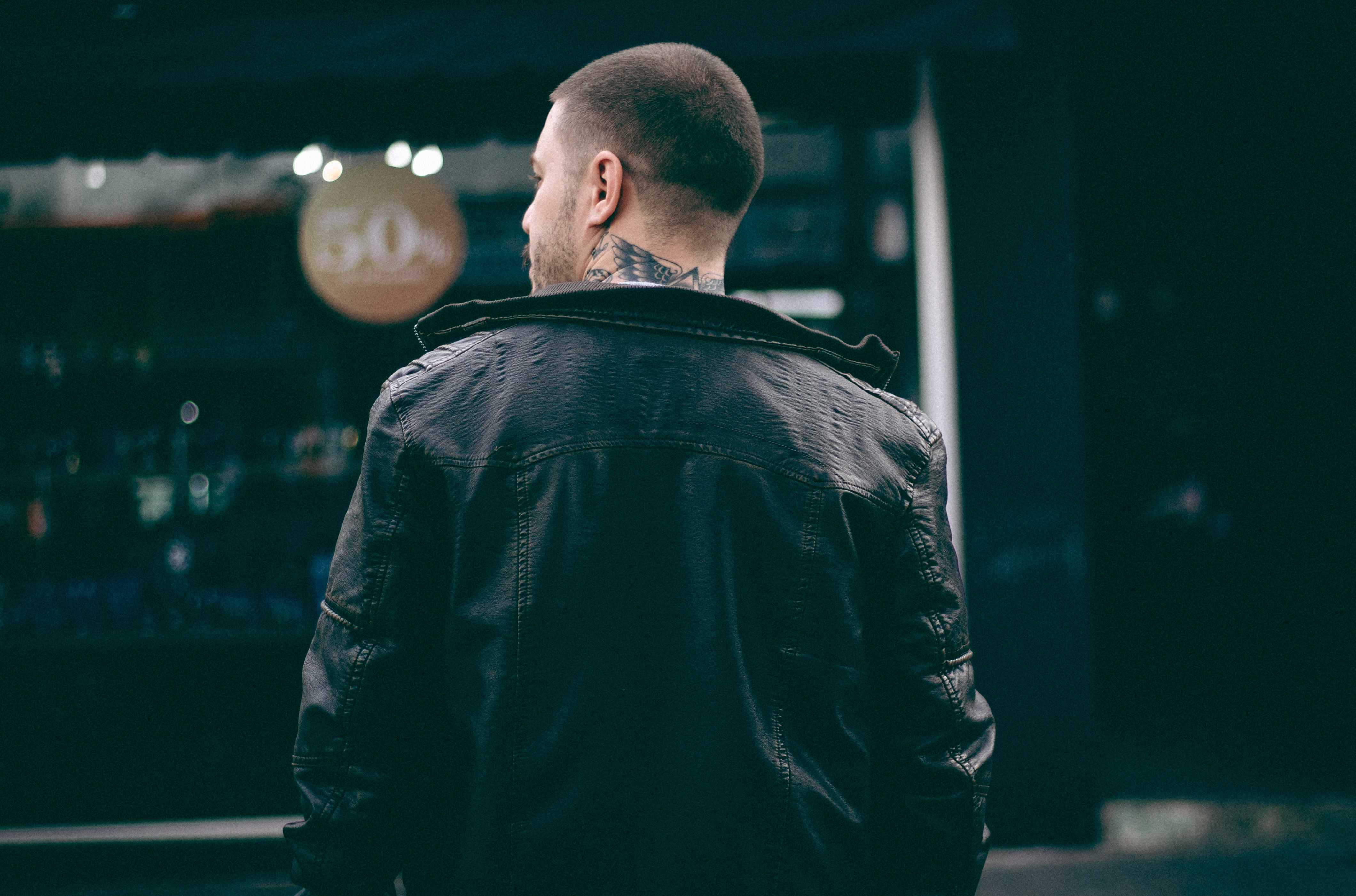 Back view of a man with a tattoo on the neck in a black leather jacket.