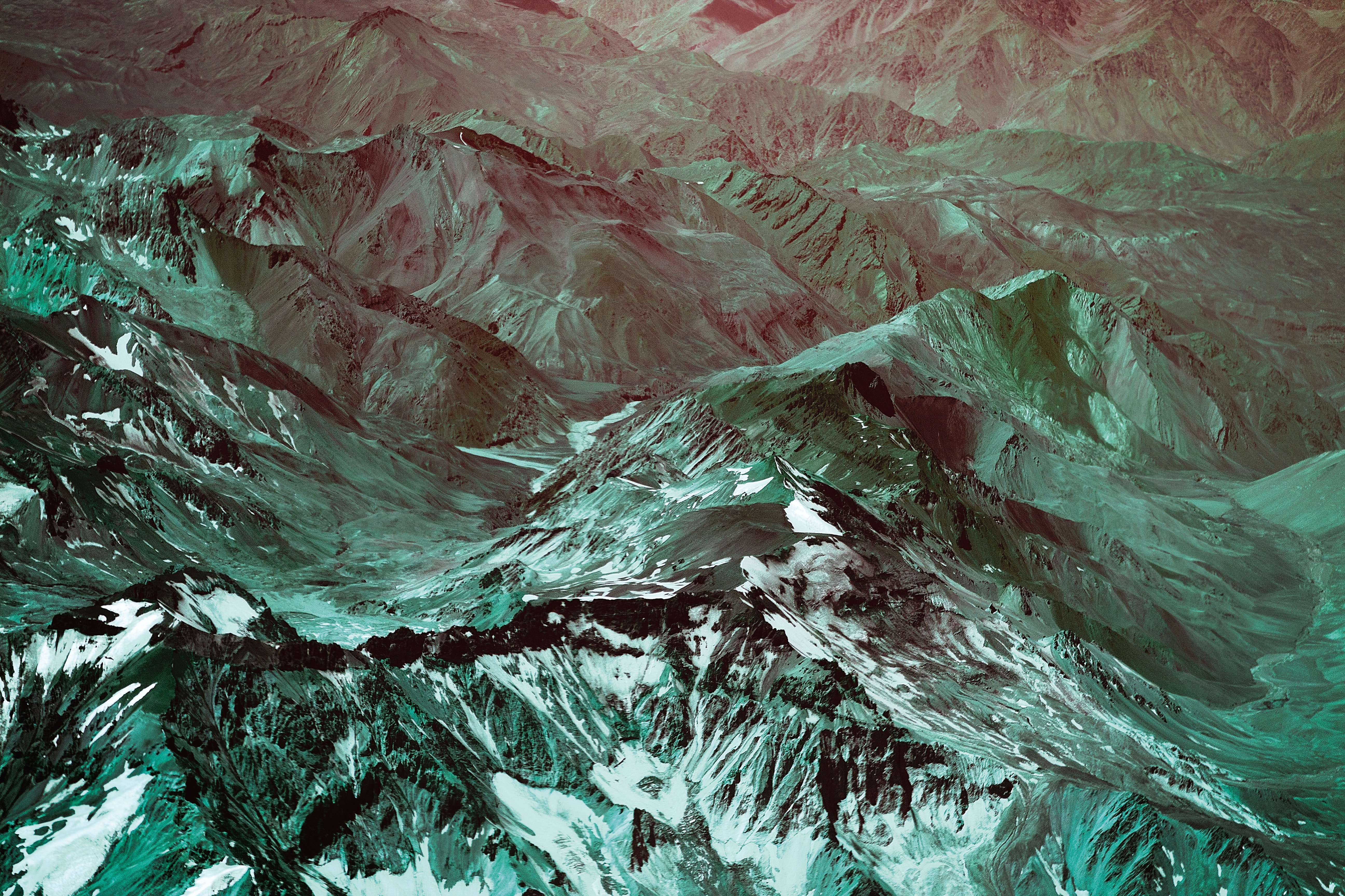 A green-hued aerial shot of the sharp ridges in the Andes