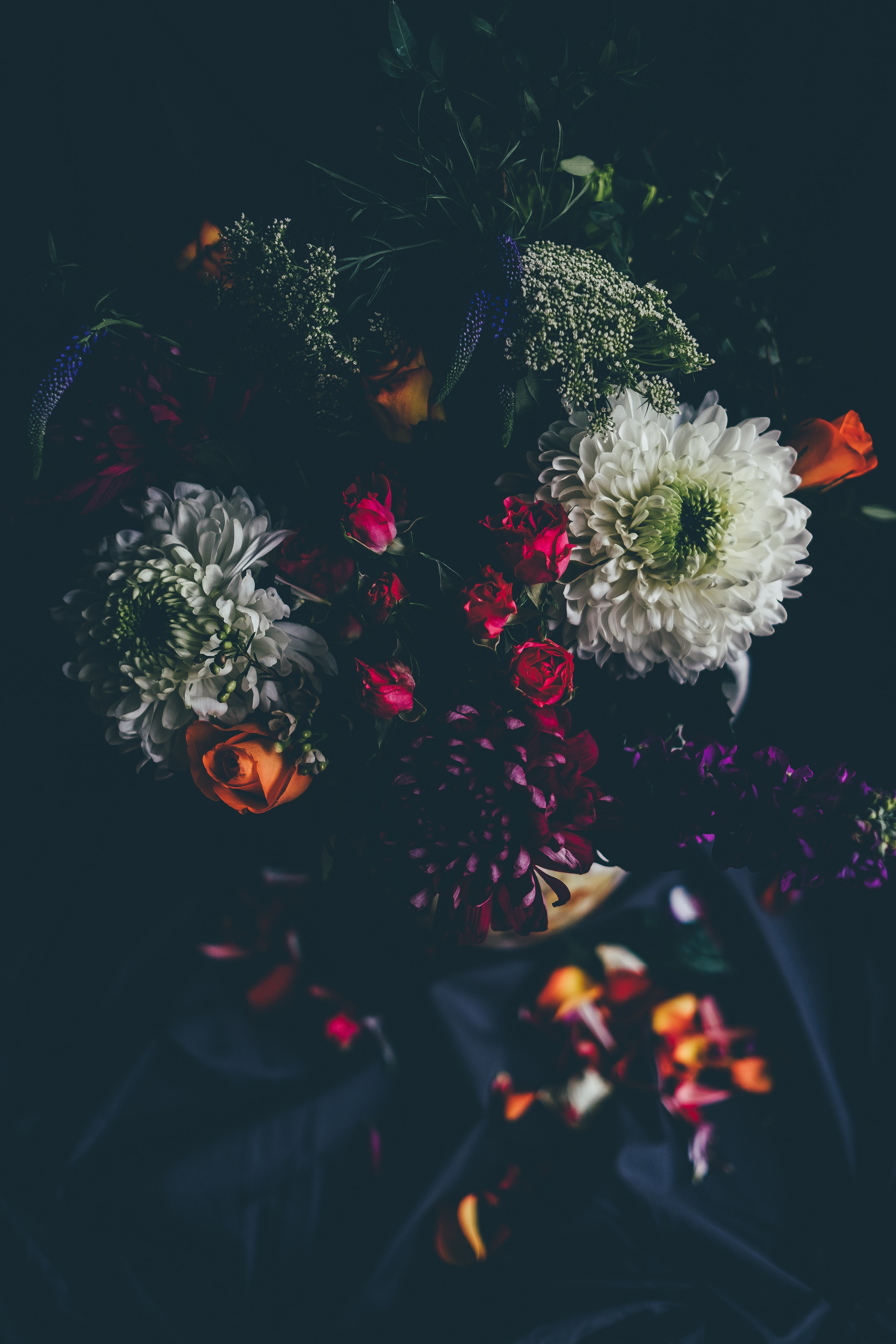 A dim shot of dahlias and roses among other flowers in a colorful bouquet