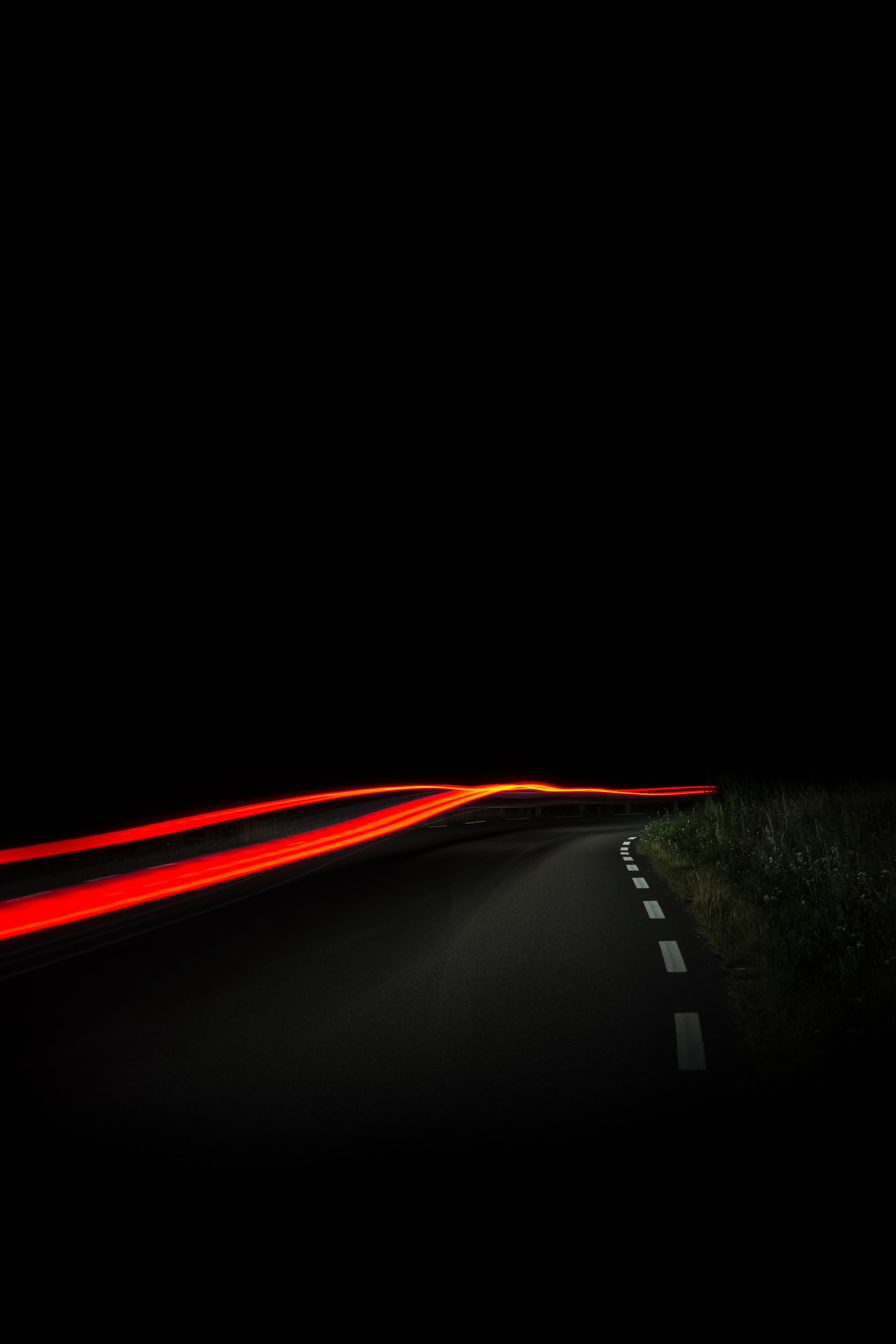 A blurry night-time shot of a road in Åsa, with red car trails amidst the street's darkness