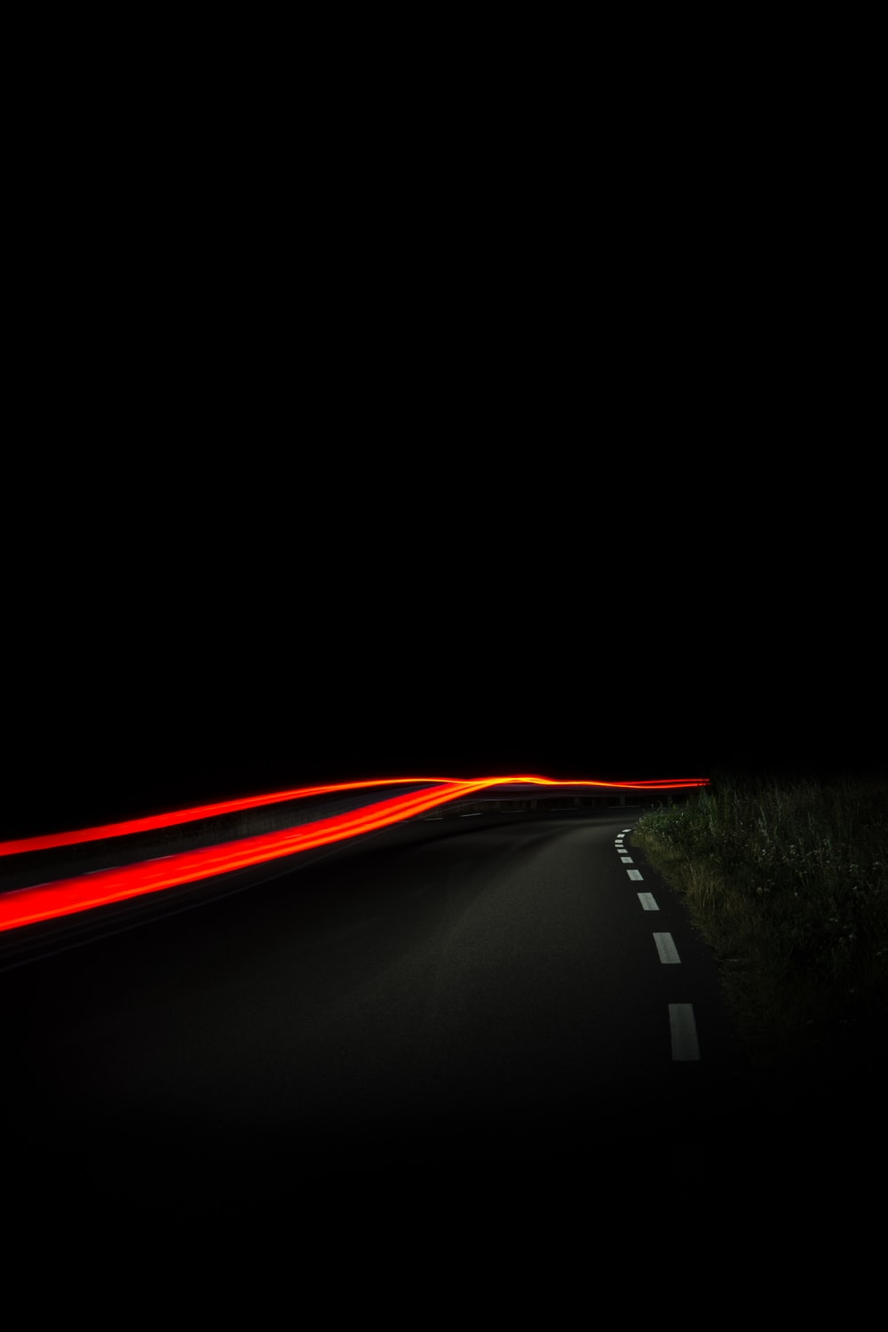 A blurry night-time shot of a road in Åsa, with red car trails