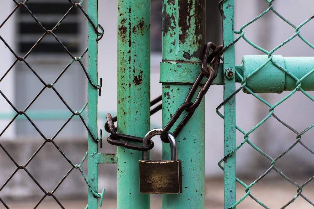 green metal gate with brown metal padlock