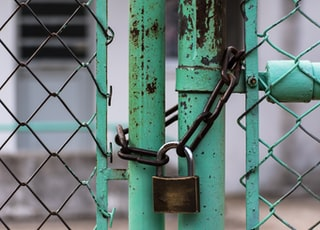 green metal gate with brown metal padlock