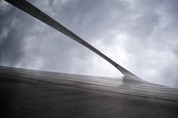 greyscale low-angle photography of arc gate under cloudy sky