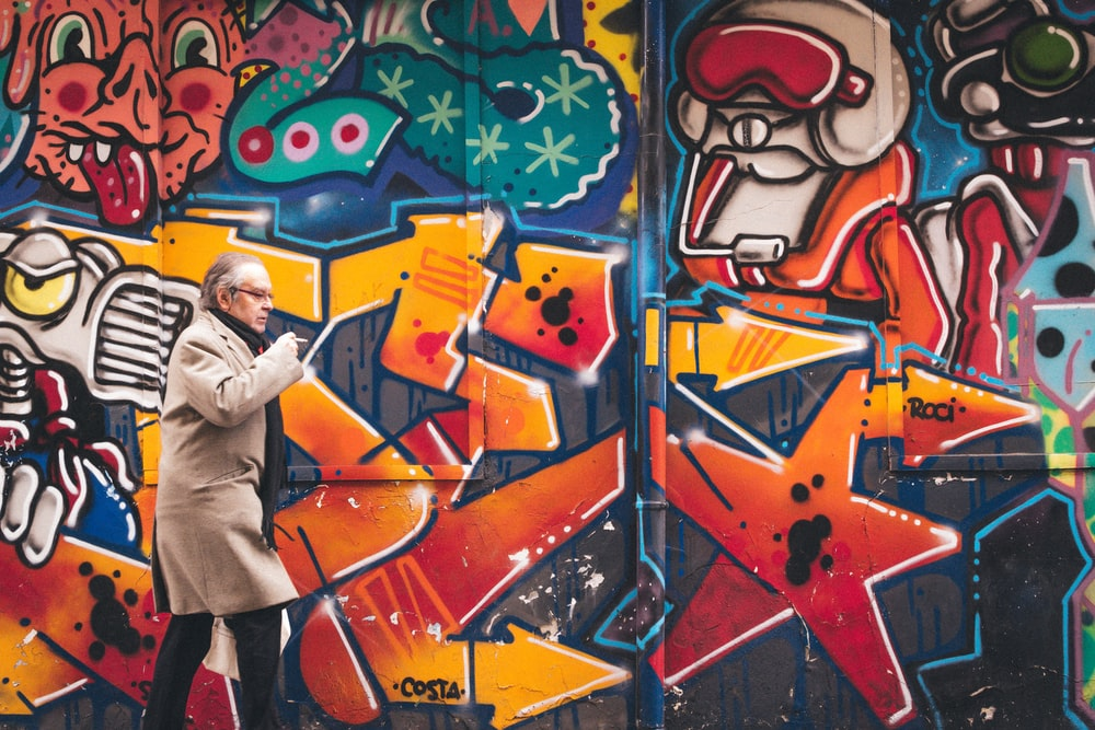 man wearing grey coat walking beside wall with graffiti