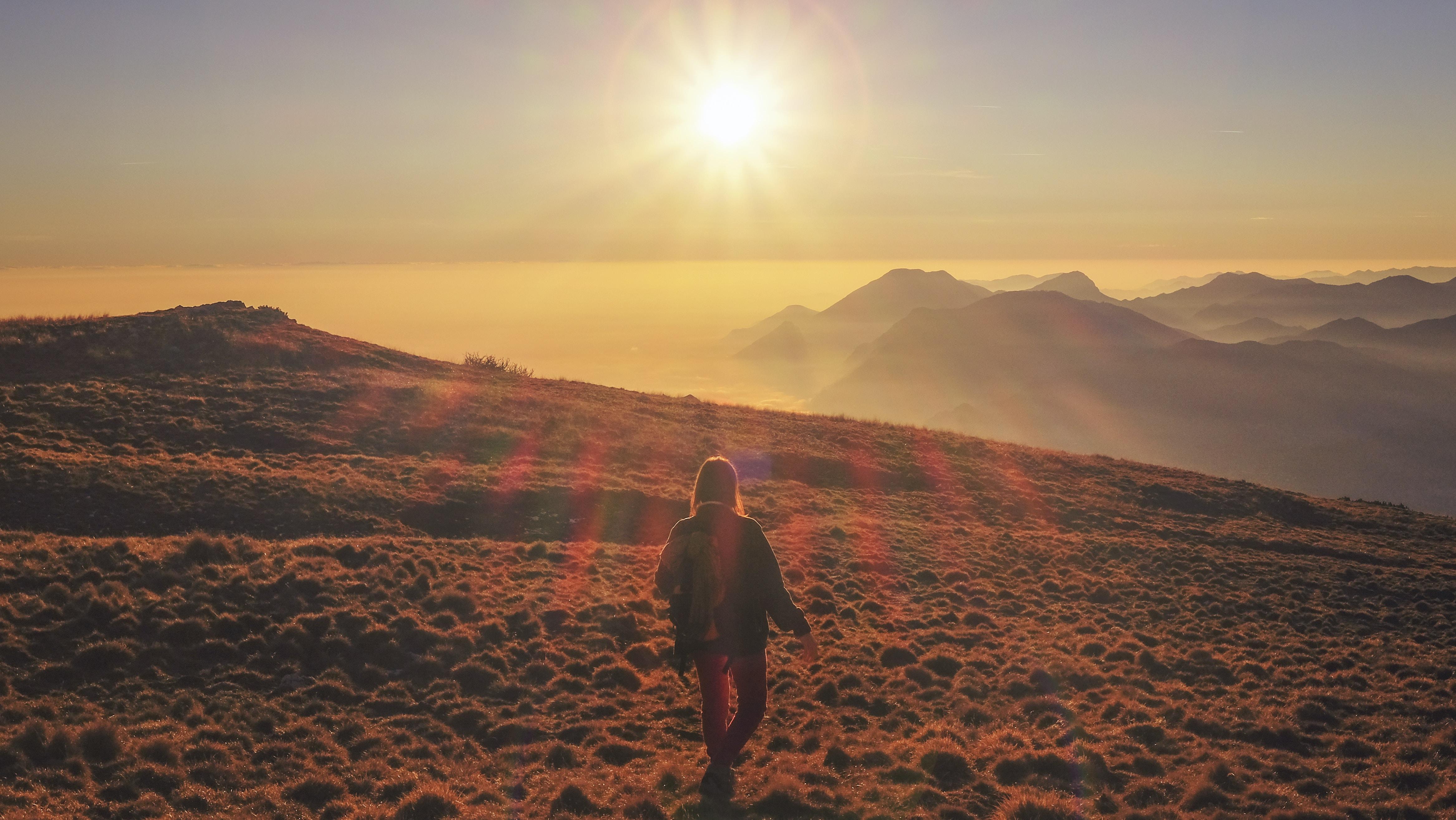 woman in blue jacket walking on desert during sunset