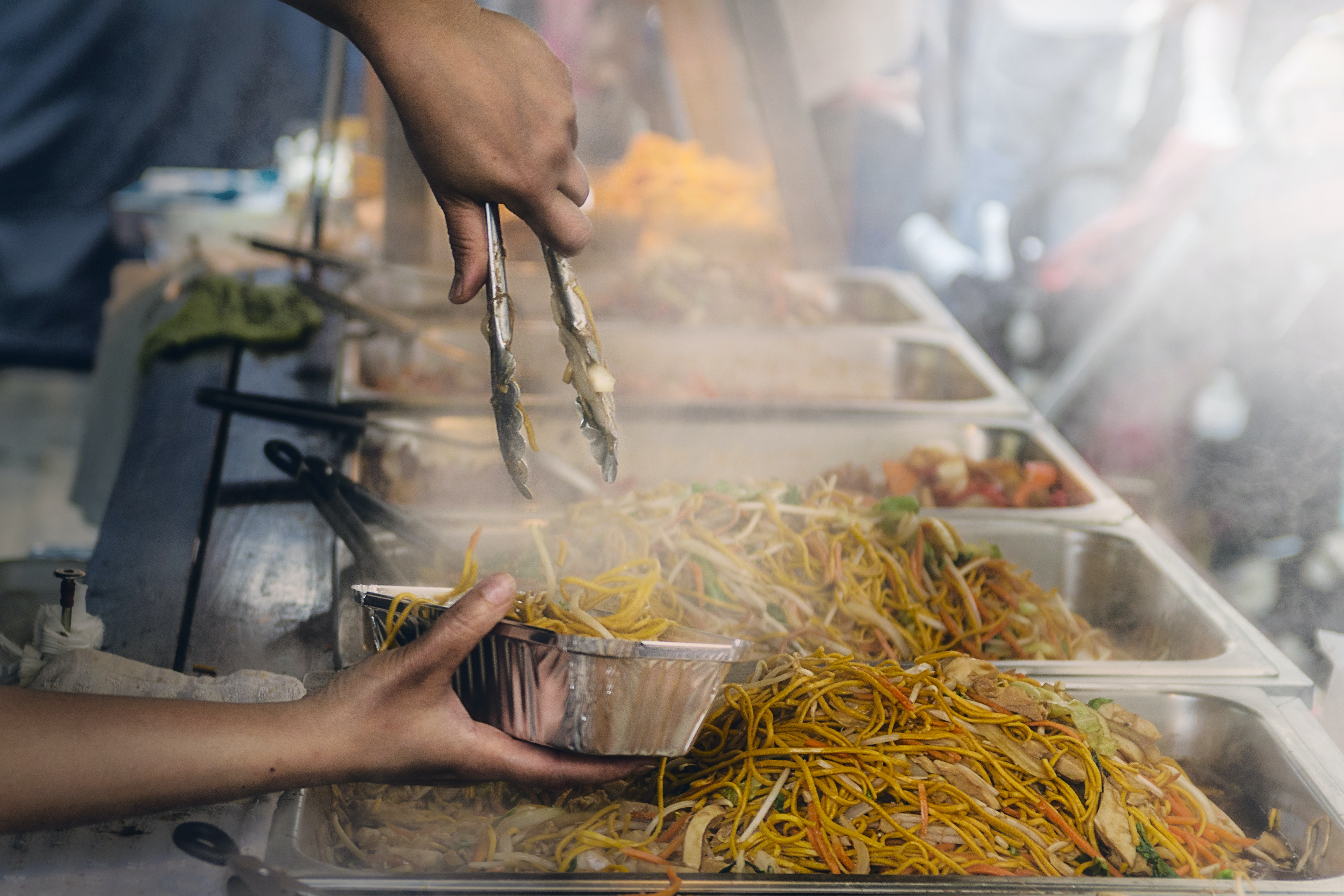 A cook putting Asian noodles into a take-out box