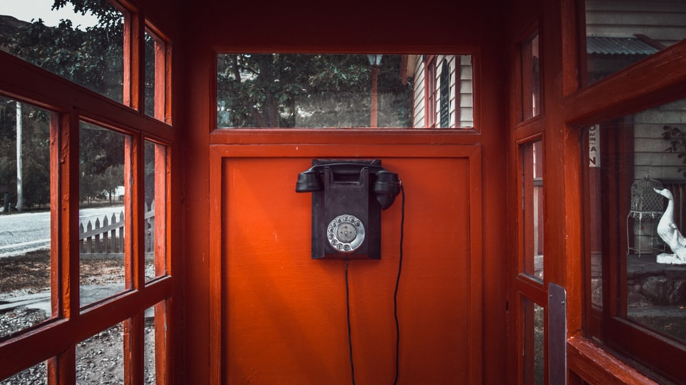 black rotary telephone mounted on red wooden wall