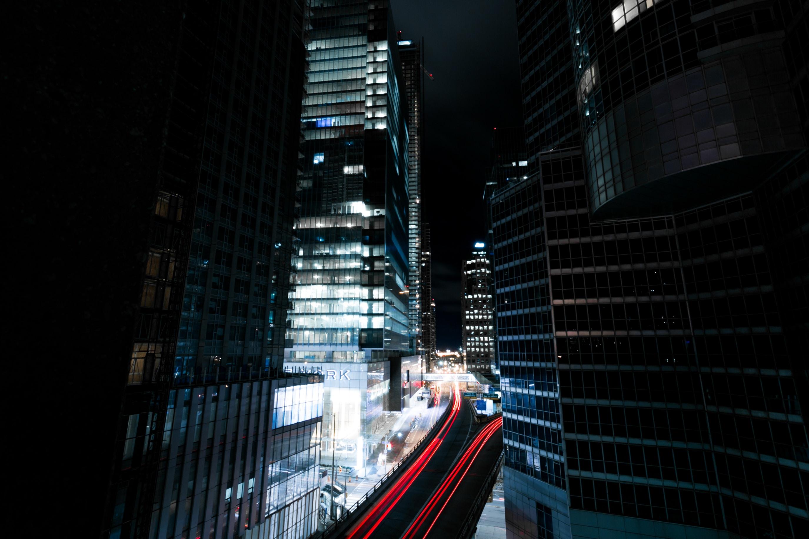 A dark photo of a dimly lit urban building with traffic light trails below