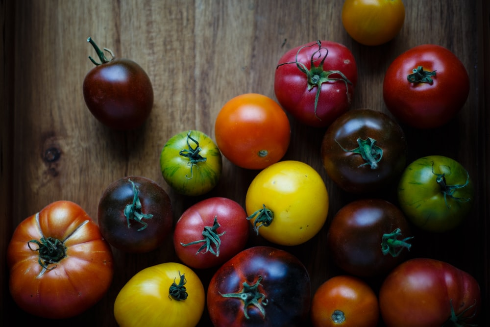 assorted-color tomatoes on brown wooden surface