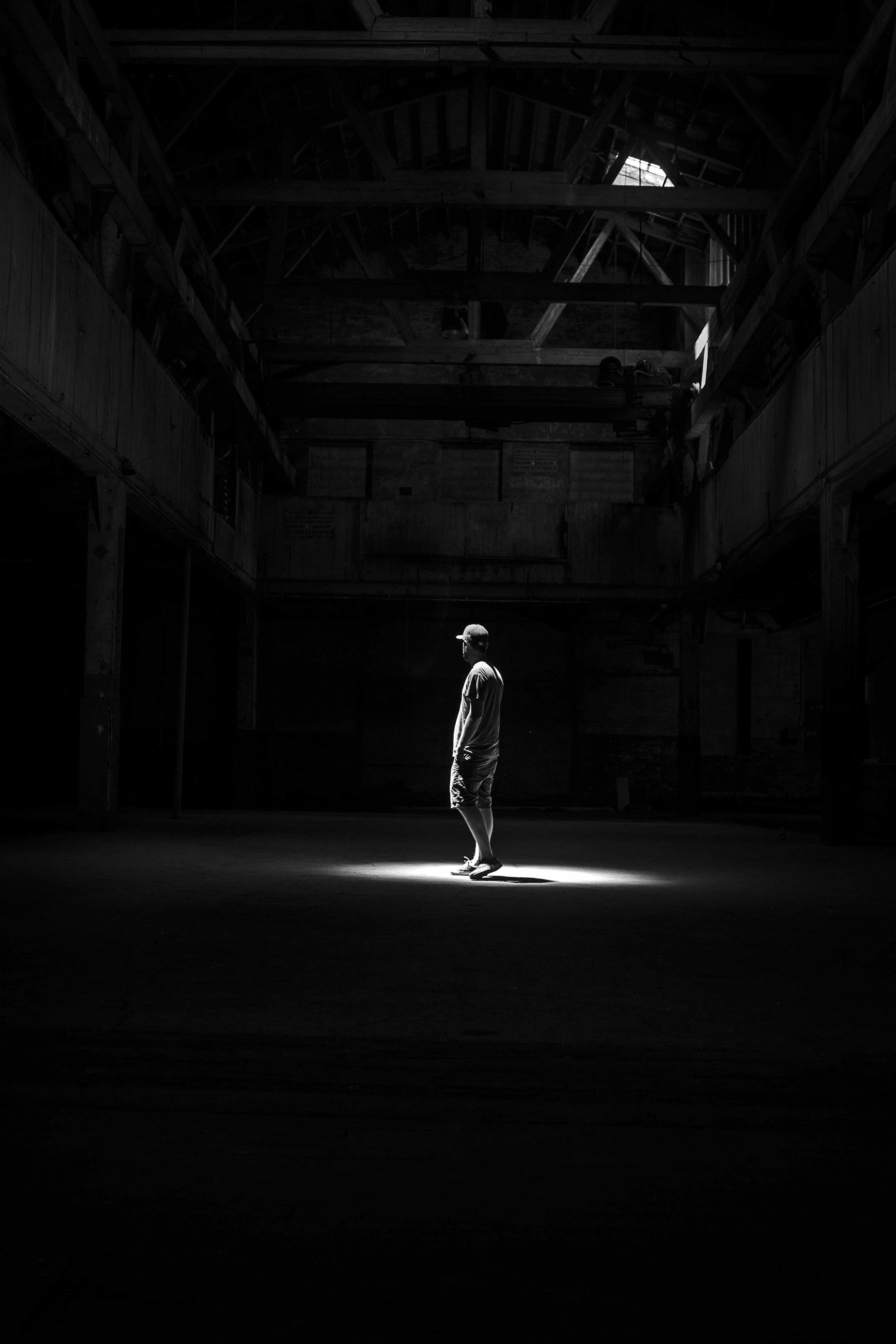 A dark black and white photo of a man standing in a building in Red Hook, Brooklyn, New York