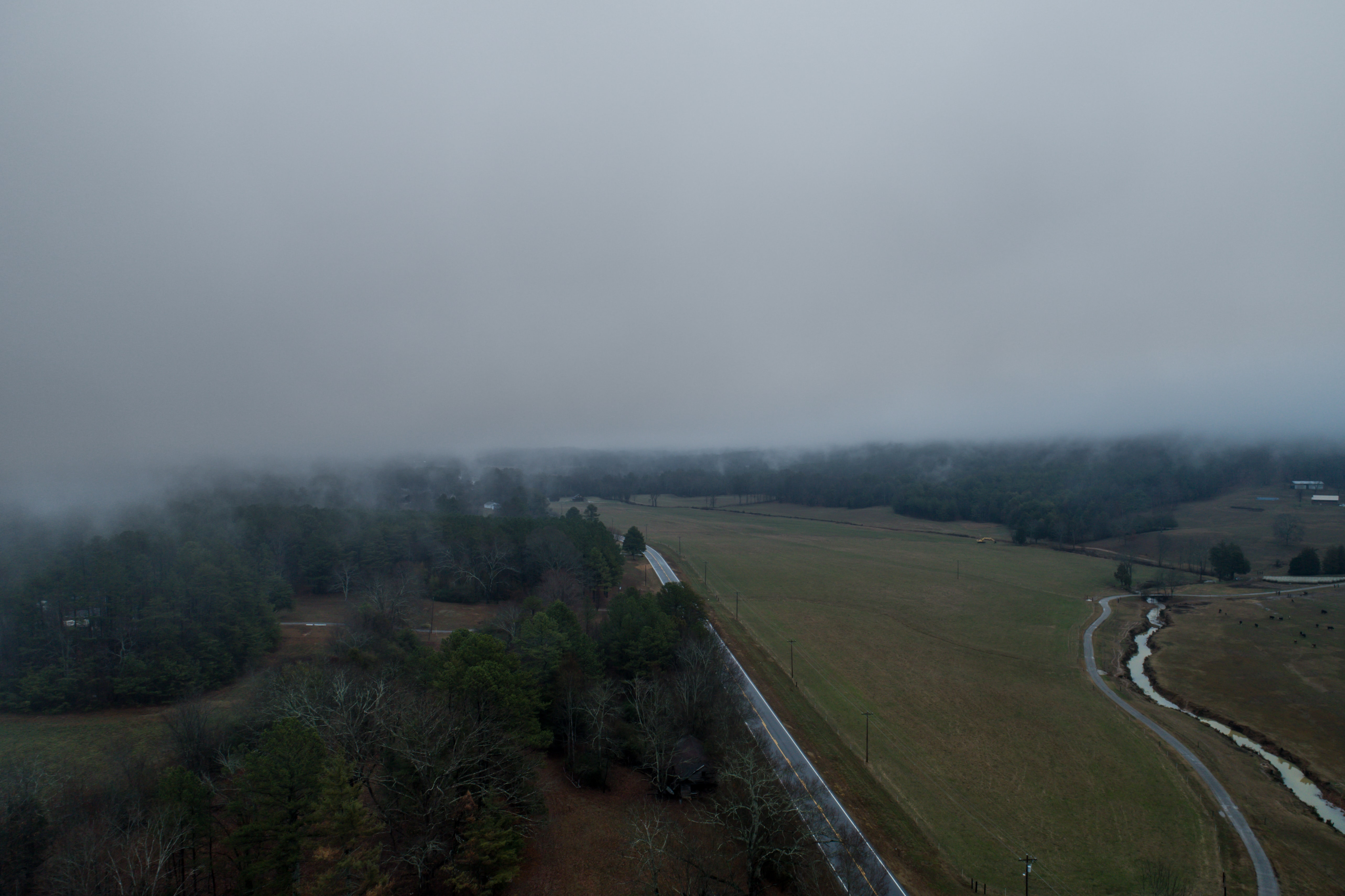 Aerial drone shot of rural fields and trees on a foggy day