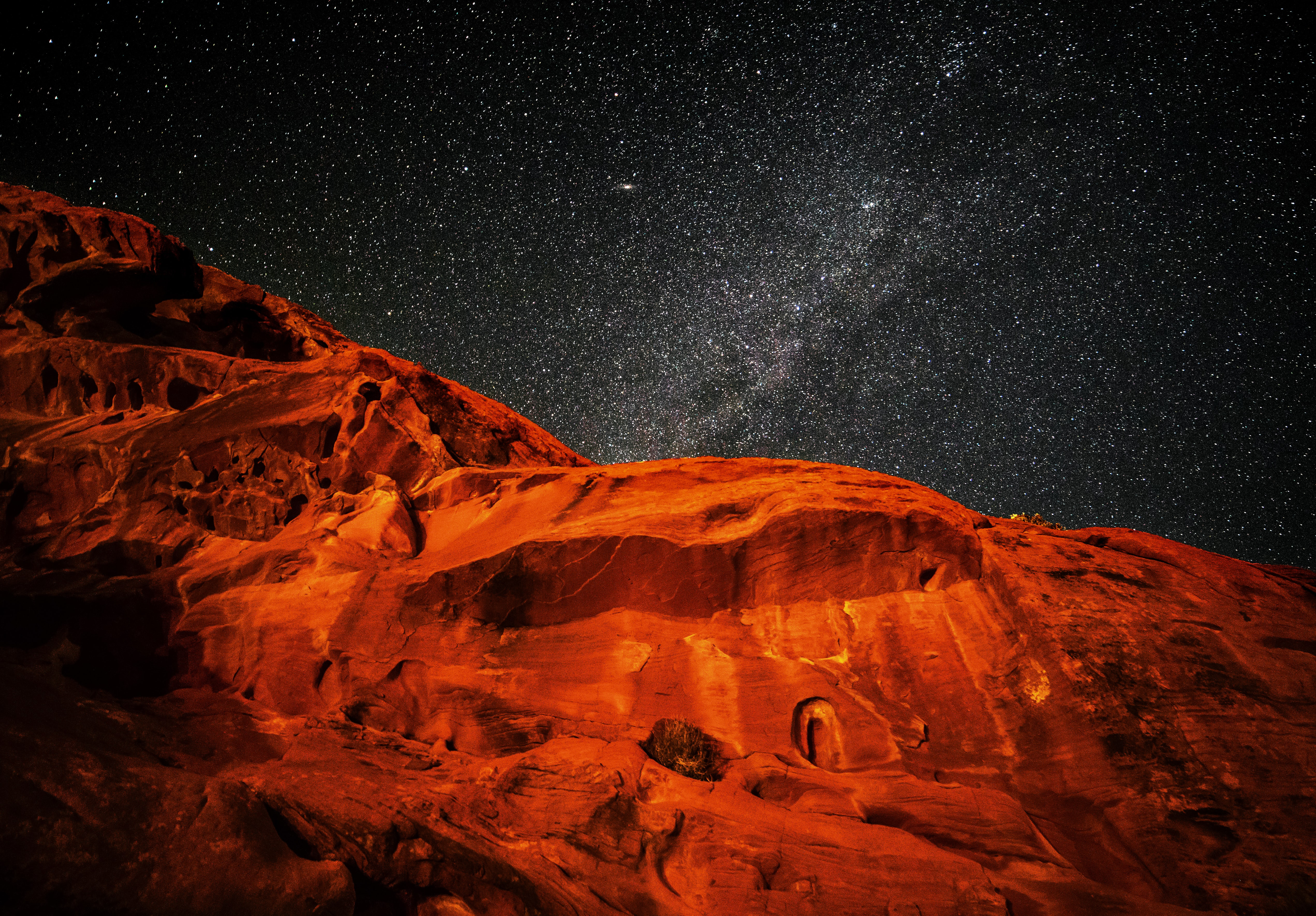 A glowing red mountain under a starry sky
