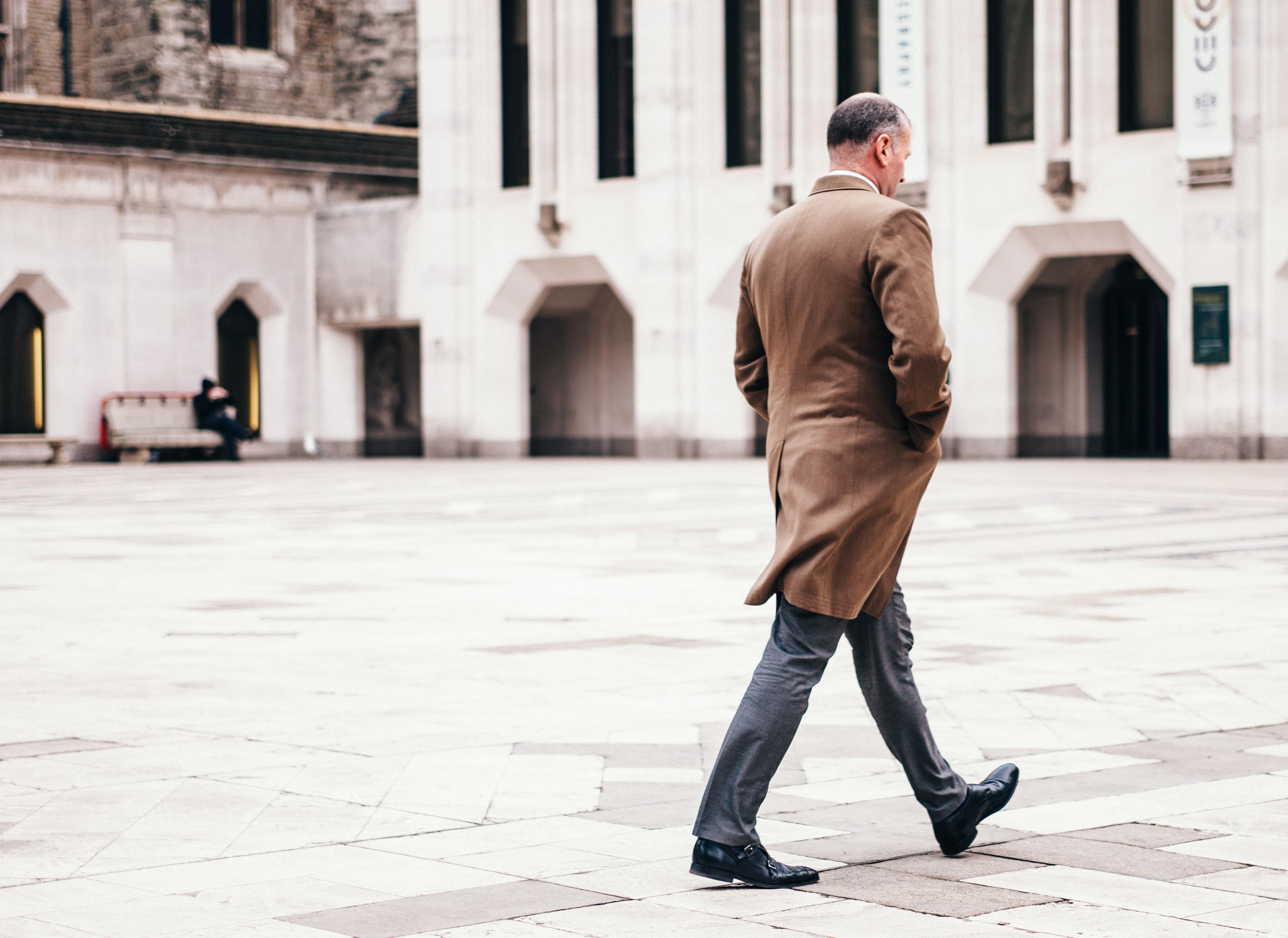 A man in a brown coat walking across an urban plaza