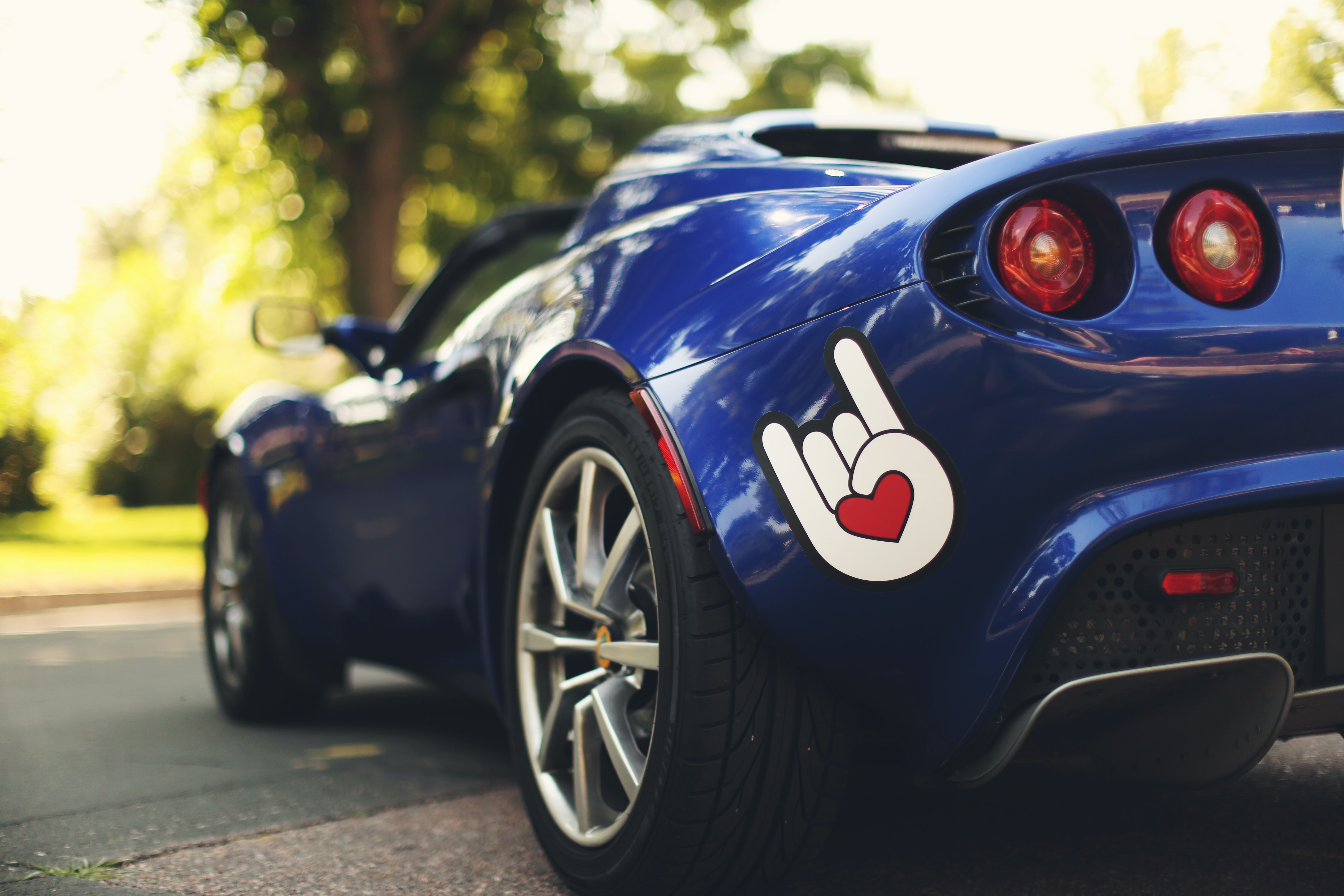 "A ""We Rock!"" hand sign with a heart in the middle on a blue sports car in Colorado Springs"
