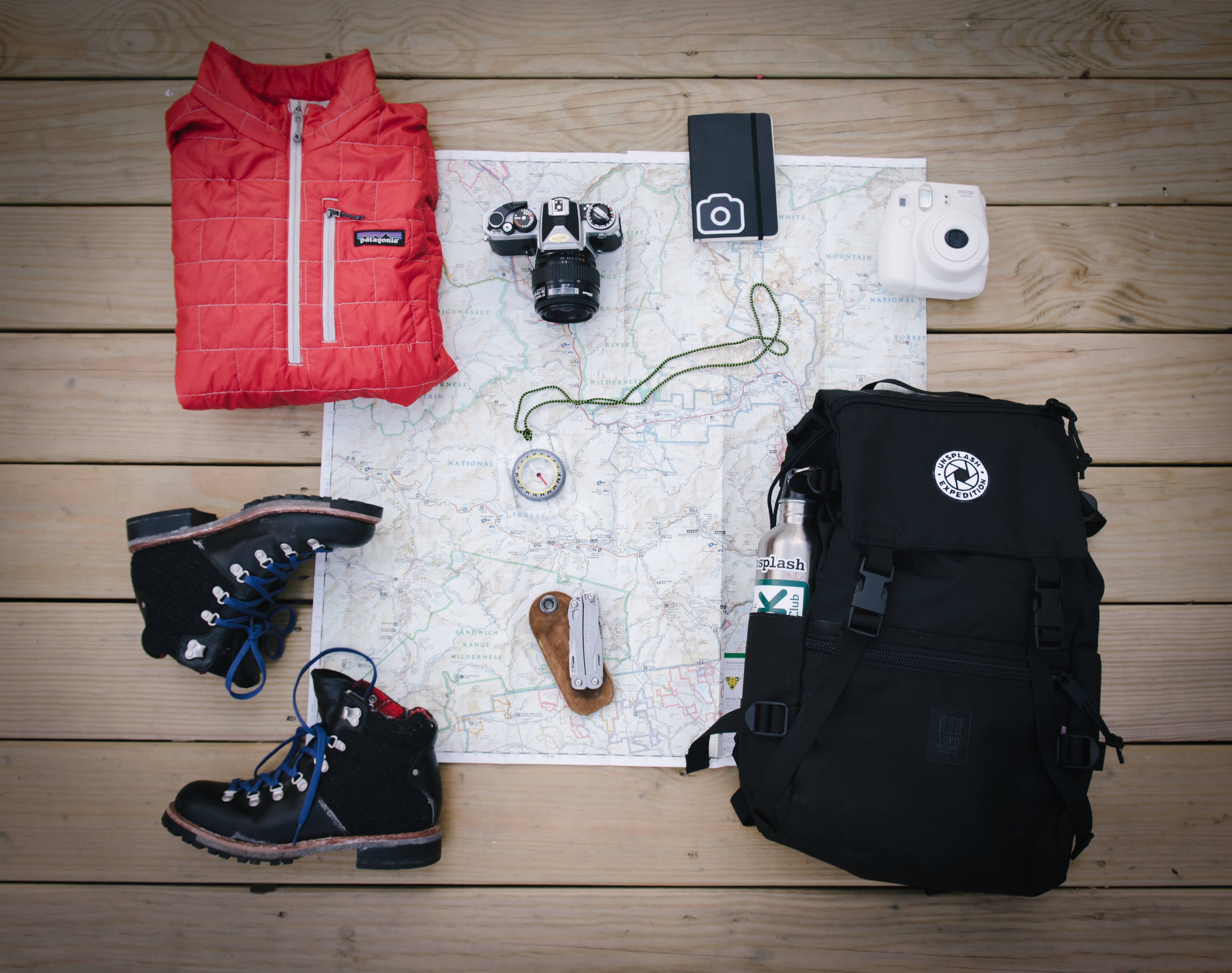 Expedition gear including a backpack, boots, jacket, camera, compass, and map