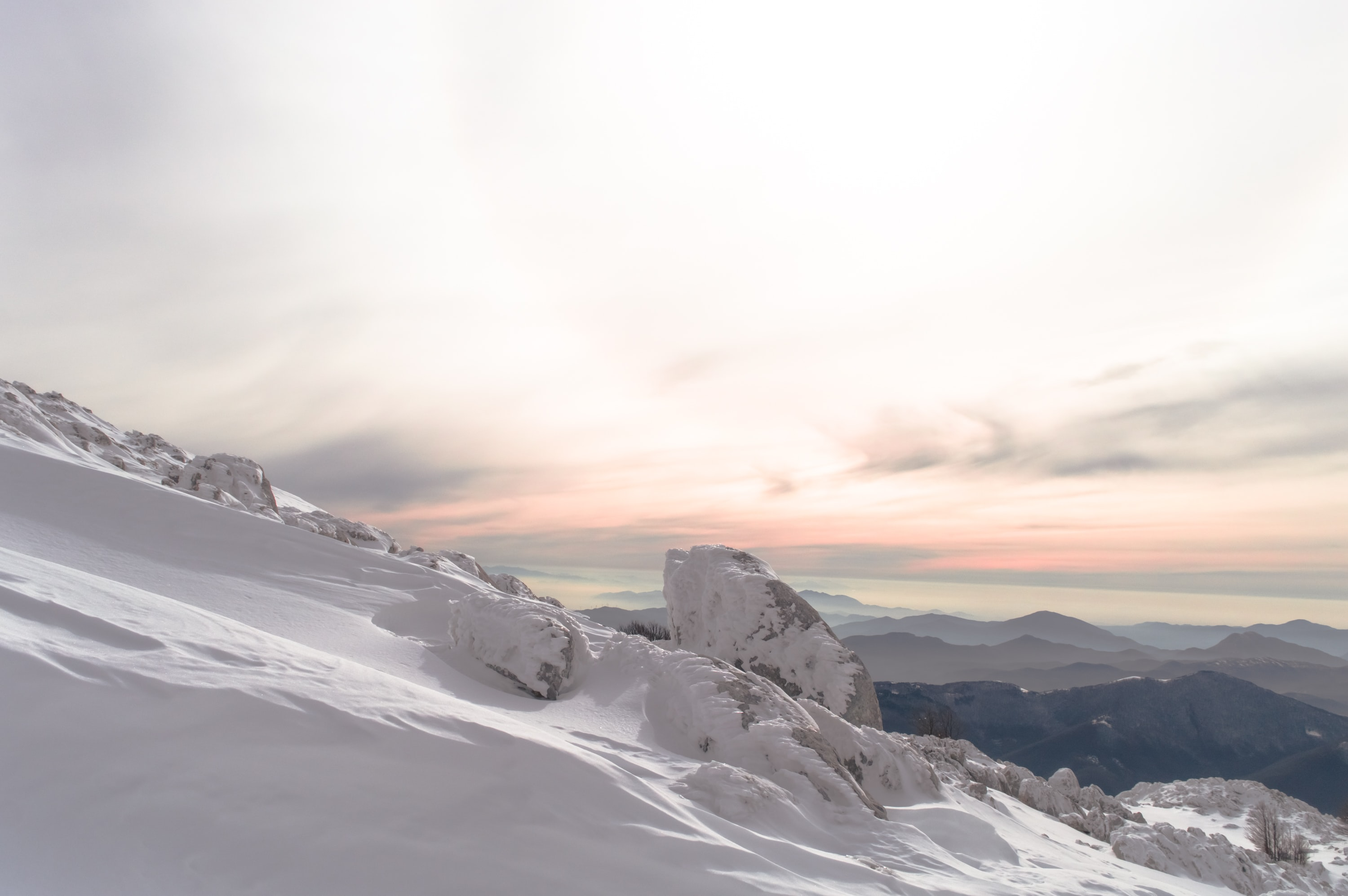 A sunset taken on top of a snow covered mountain
