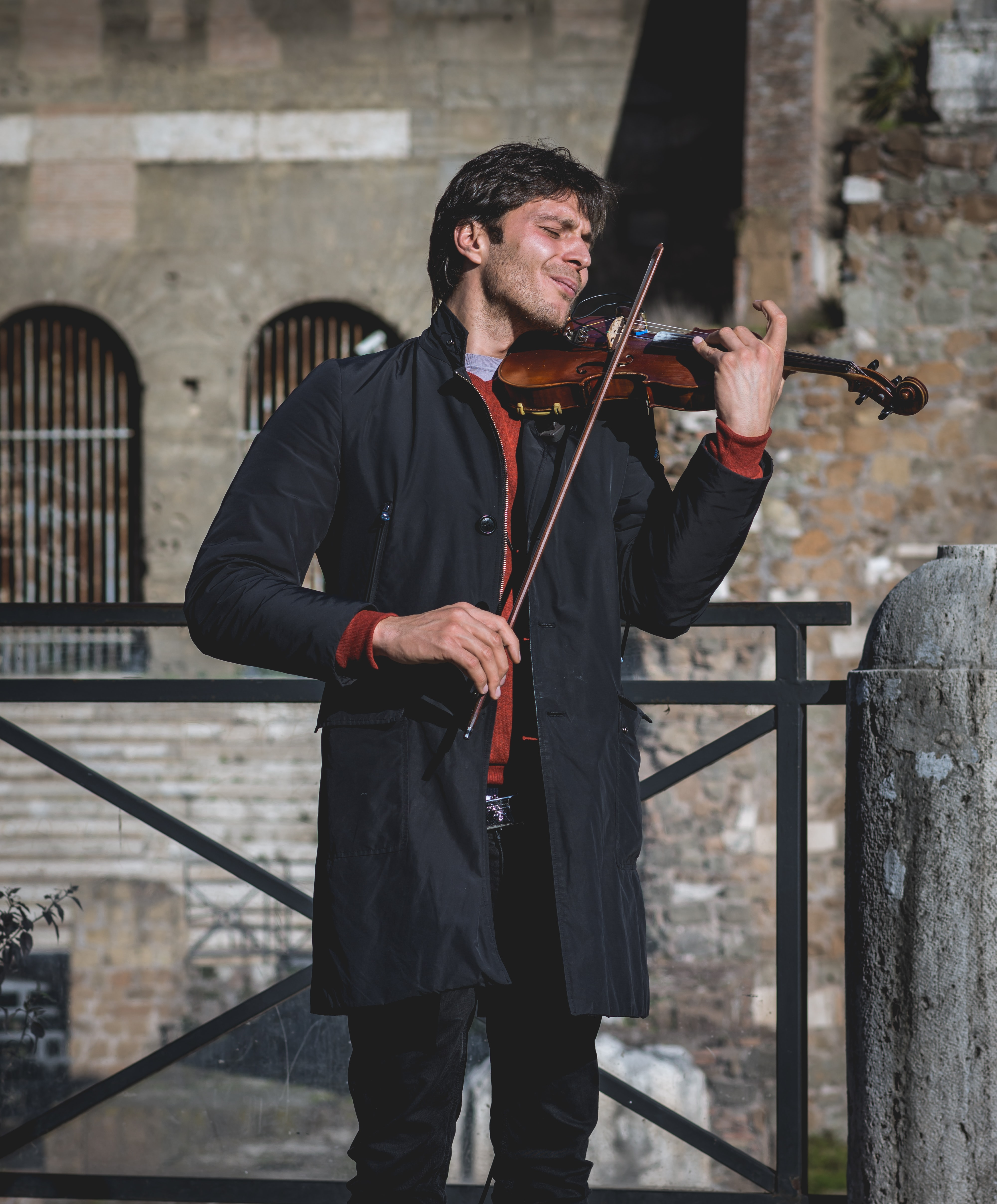 A man in a black coat playing the violet with his eyes closed in front of an old building