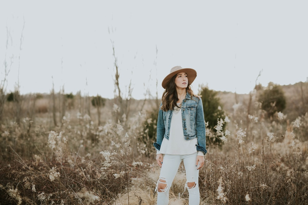 woman in blue denim jacket surrounded by grass during daytime