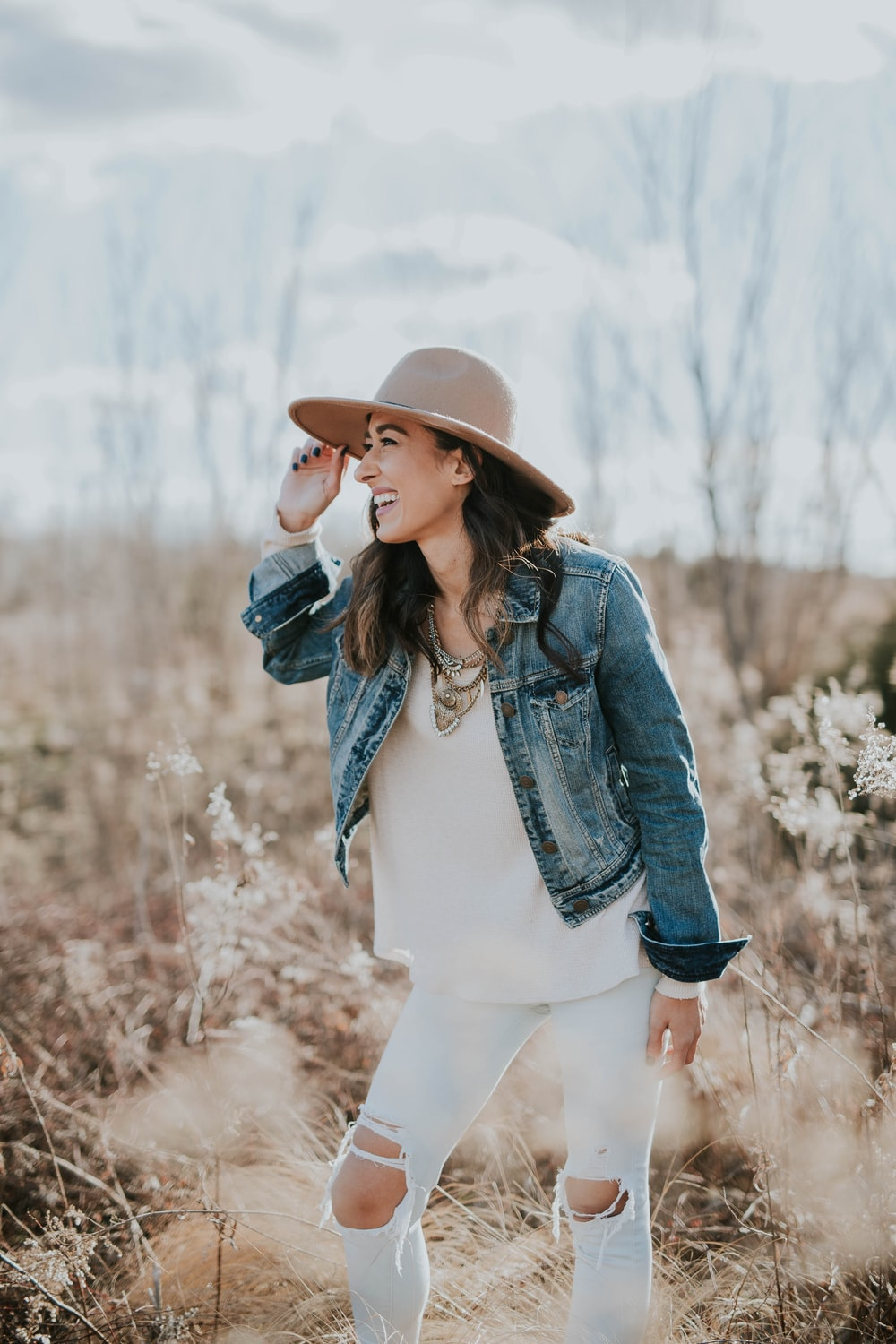 woman standing on dried grass facing right while holding her brown sun hat during daytime