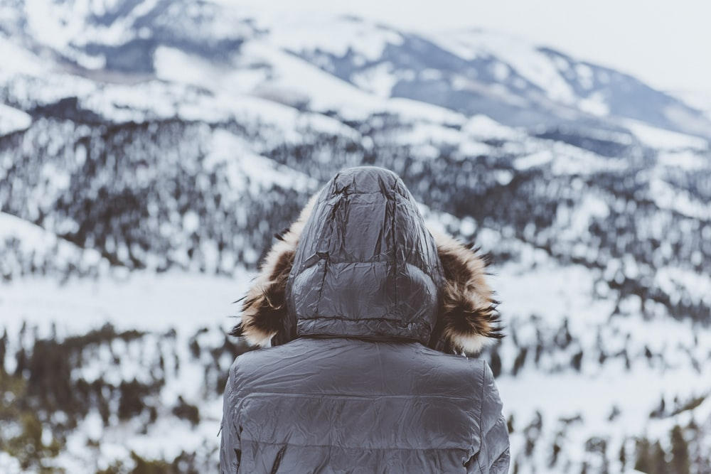 person wearing black parka hoodie in front of mountain