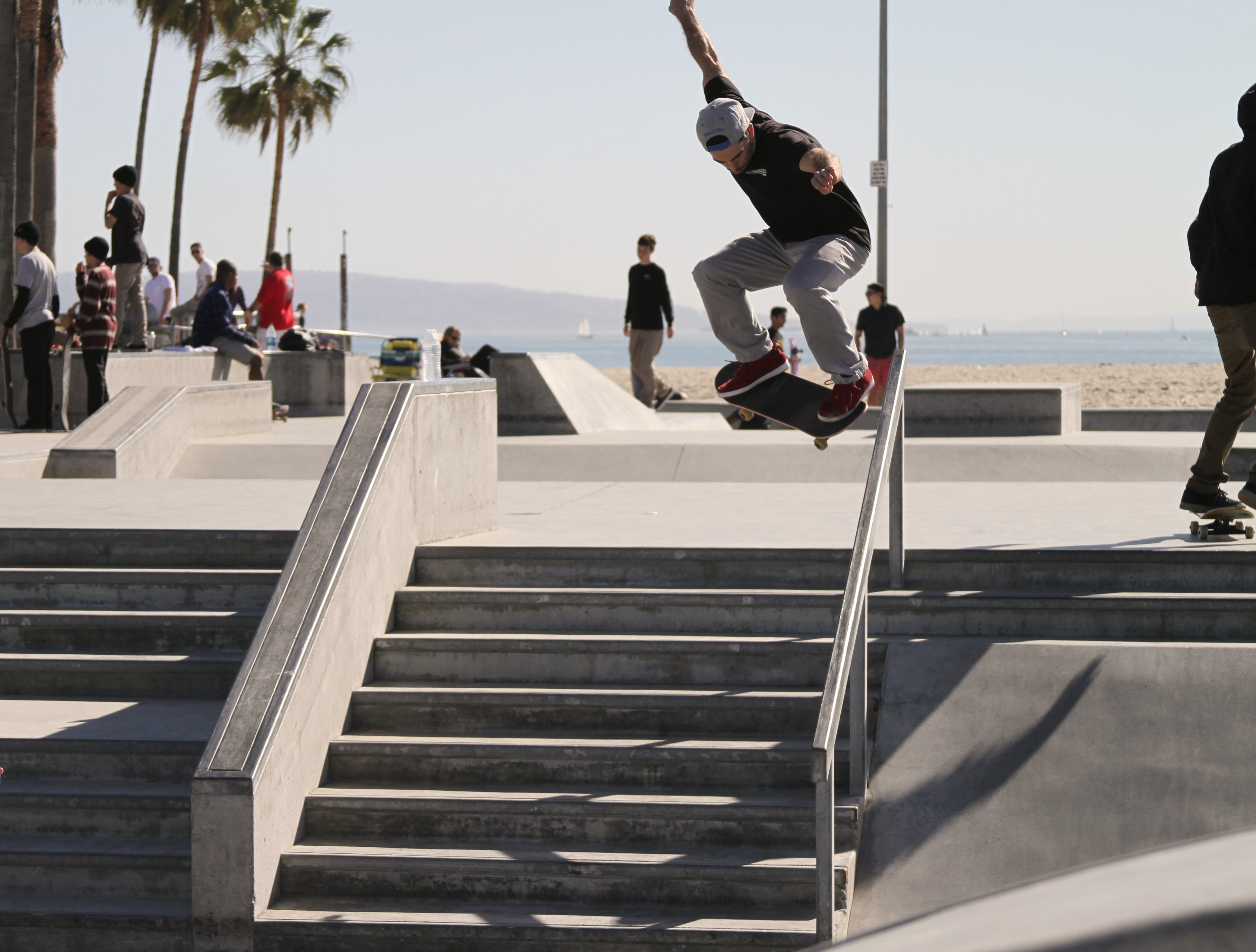 Skater in mid-air above the stairs and a rail at Venice