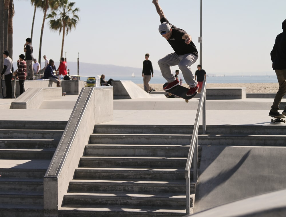 person riding skateboard performing stunt over stairs