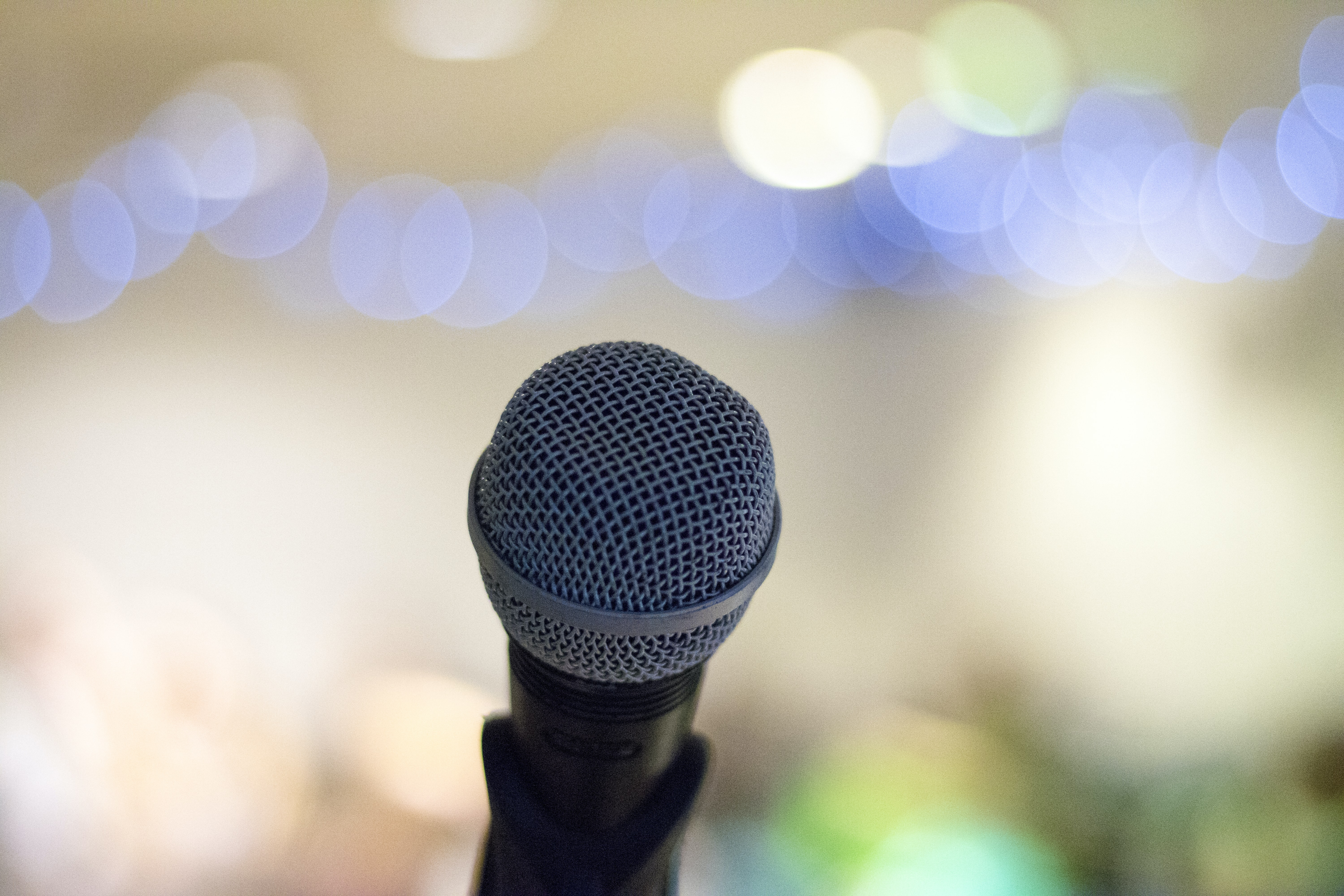 An microphone in a stand with bokeh effect in the background