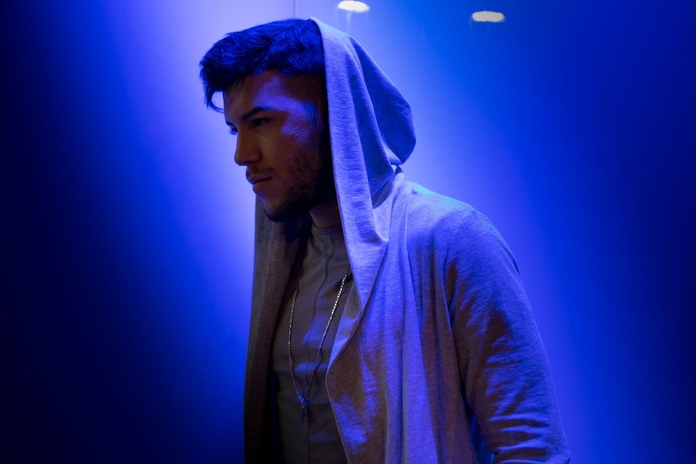 man i hood on standing on blue background