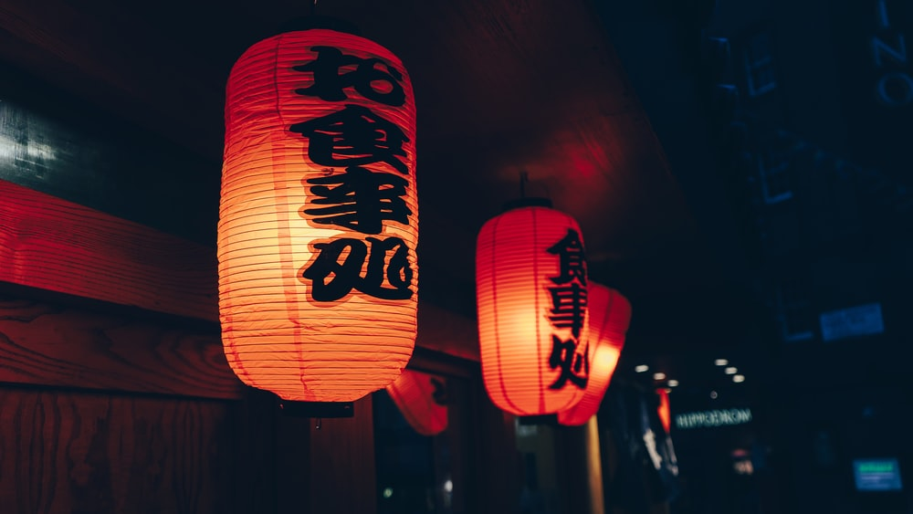 close-up photography of two orange paper lanterns with kanji script