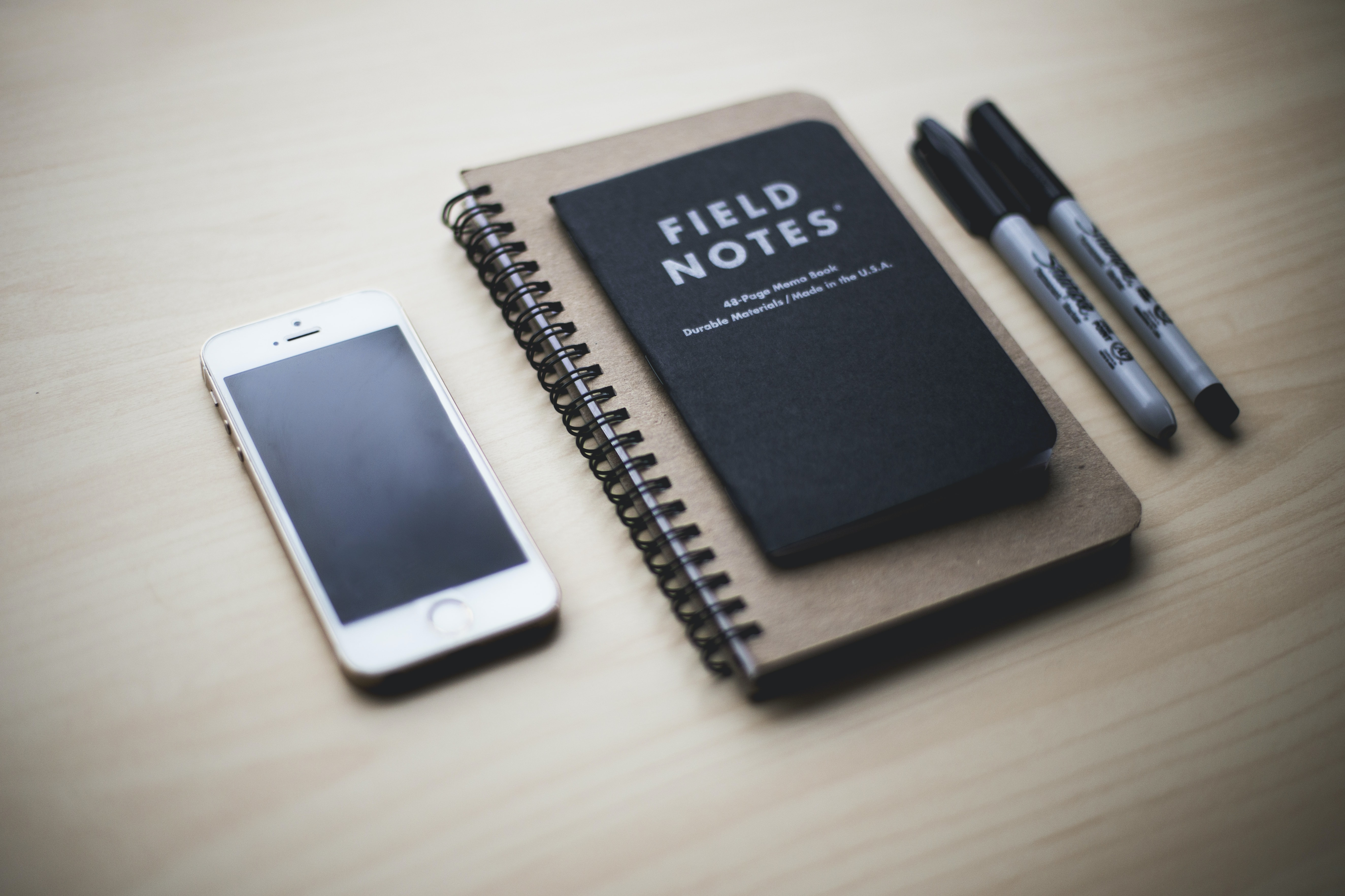 A Field Notes memo book on top of a larger spiral notebook with two sharpies on the right and a phone on the left