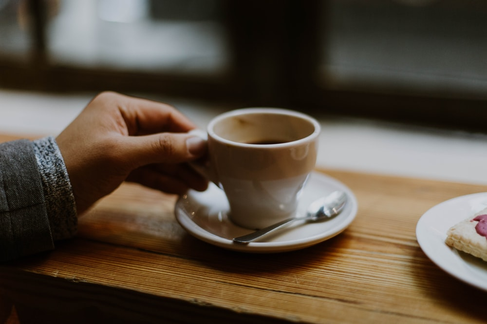 person holding white ceramic tea cup
