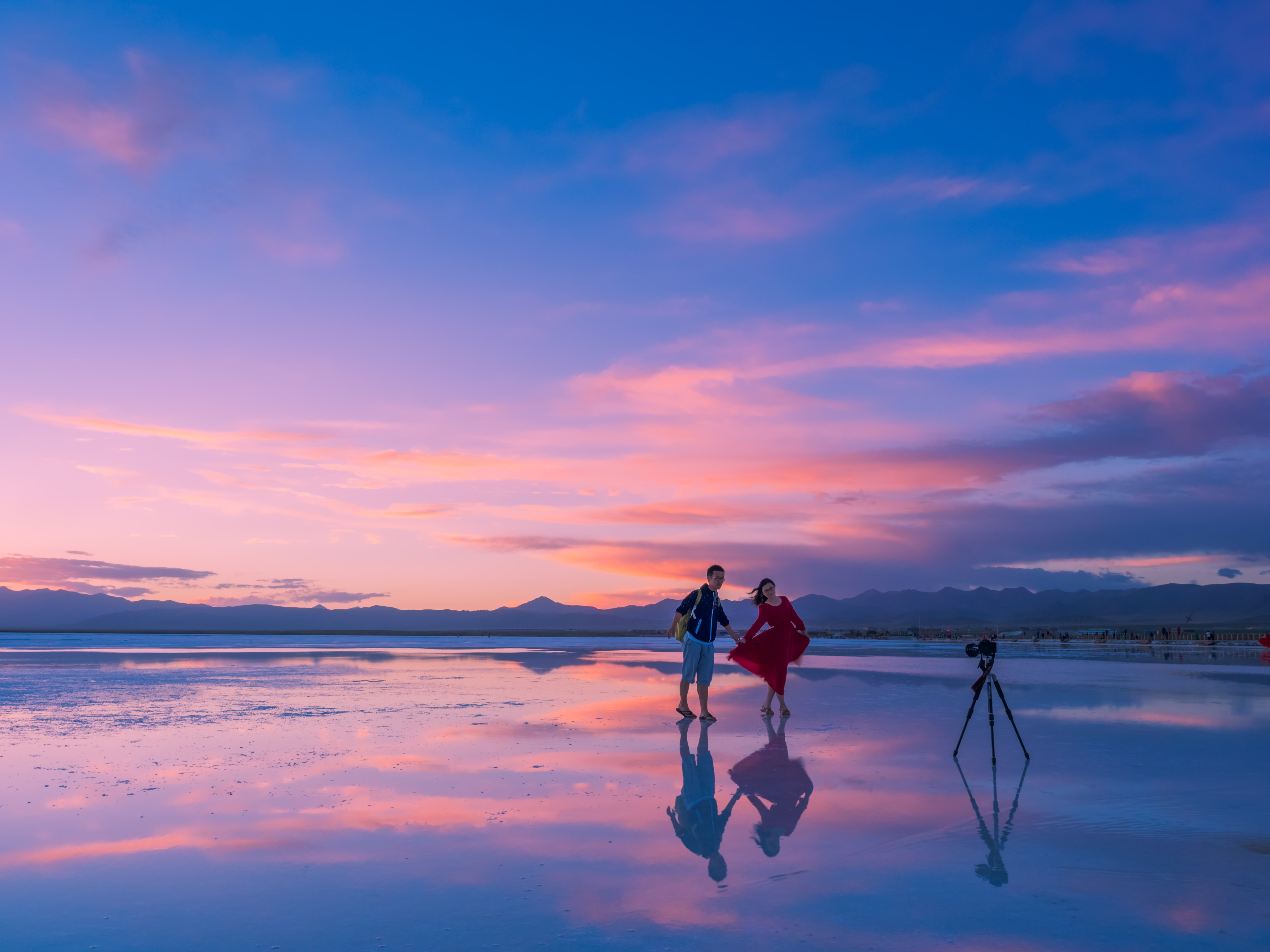 View of the couple posing in front of the camera on a tripod on a sand beach after sunset