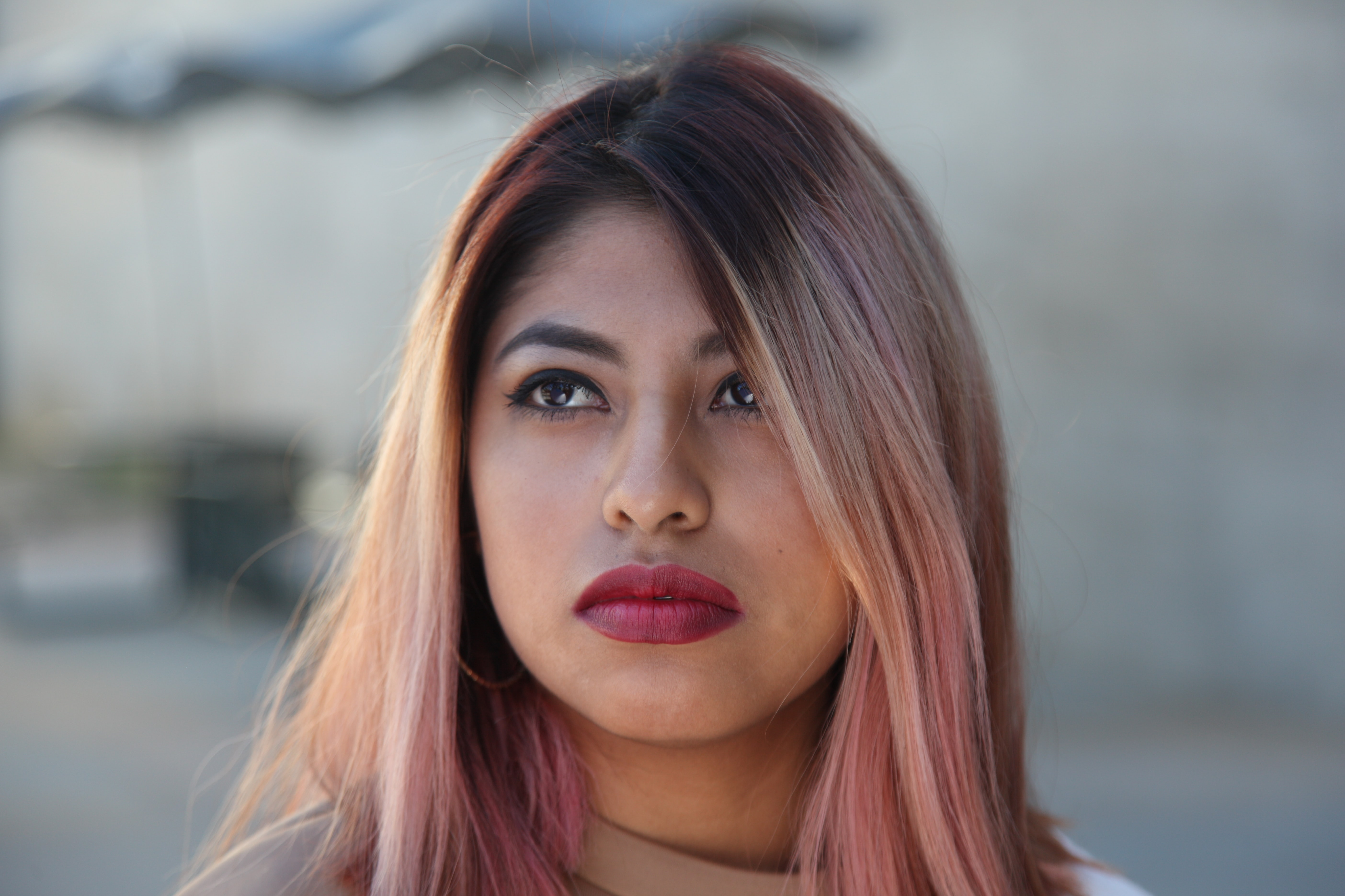 Woman with bold pink lips and pink hair looking away